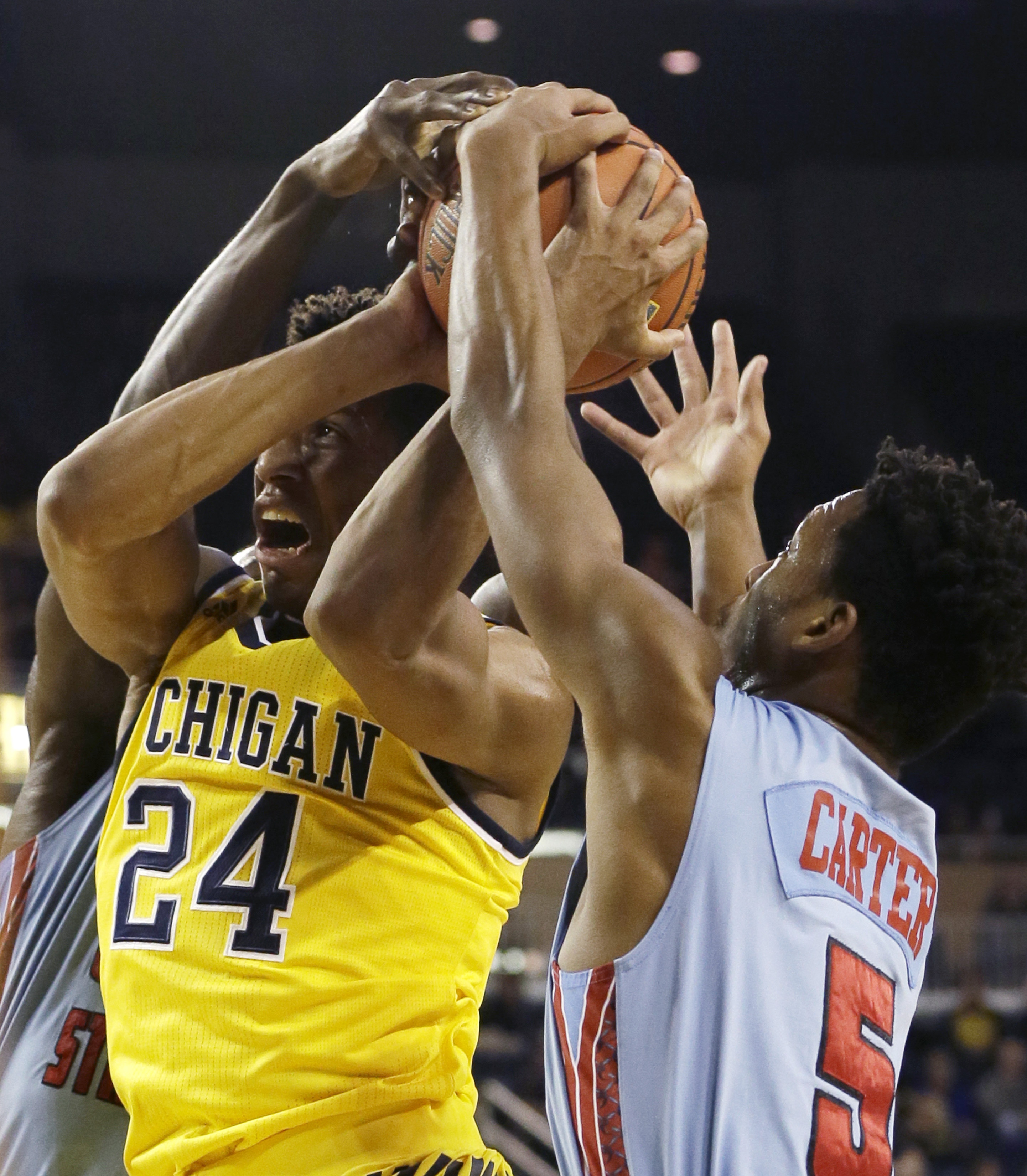 Michigan guard Aubrey Dawkins (24) and Delaware State guard Malik Carter (5) battle for a rebound during the second half of an NCAA college basketball game, Saturday, Dec. 12, 2015, in Ann Arbor, Mich. (AP Photo/Carlos Osorio)