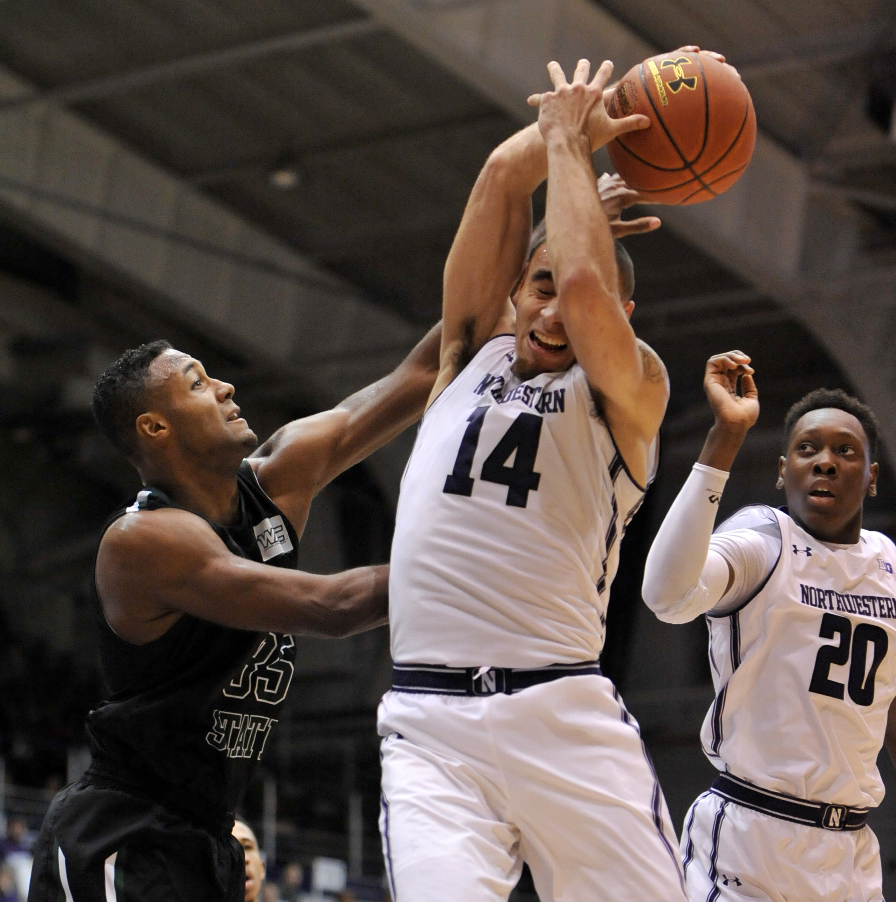 Northwestern's Tre Demps (14), battles Chicago State's Devon Friend (35), for a rebound while Northwestern's Scottie Lindsey (20), looks on during the first half of a basketball game Sunday, Dec. 13, 2015, in Evanston, Ill. (AP Photo/Paul Beaty)