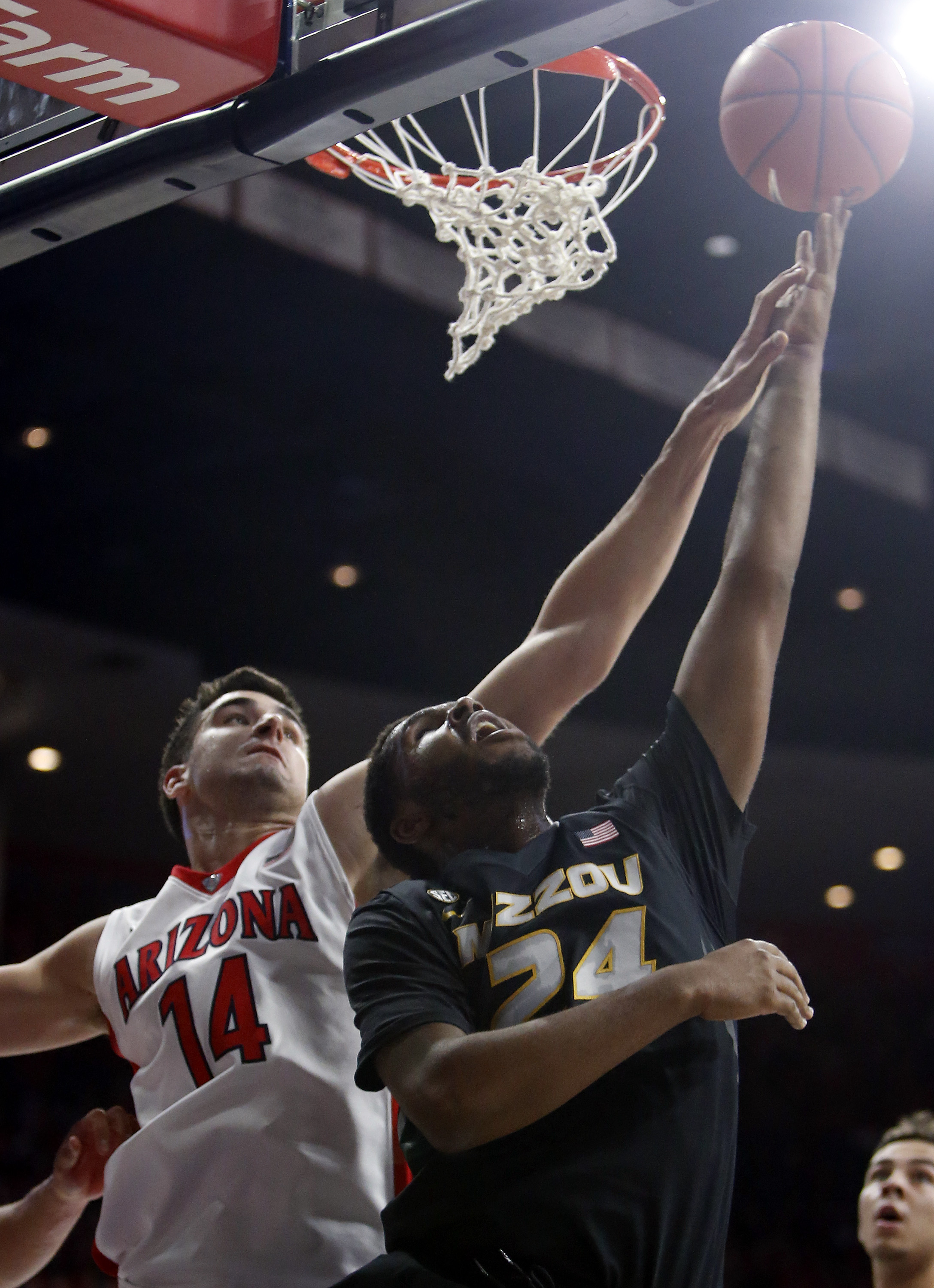 Missouri forward Kevin Puryear shoots in front of Arizona center Dusan Ristic (14) during the first half of an NCAA college basketball game, Sunday, Dec. 13, 2015, in Tucson, Ariz. (AP Photo/Rick Scuteri)