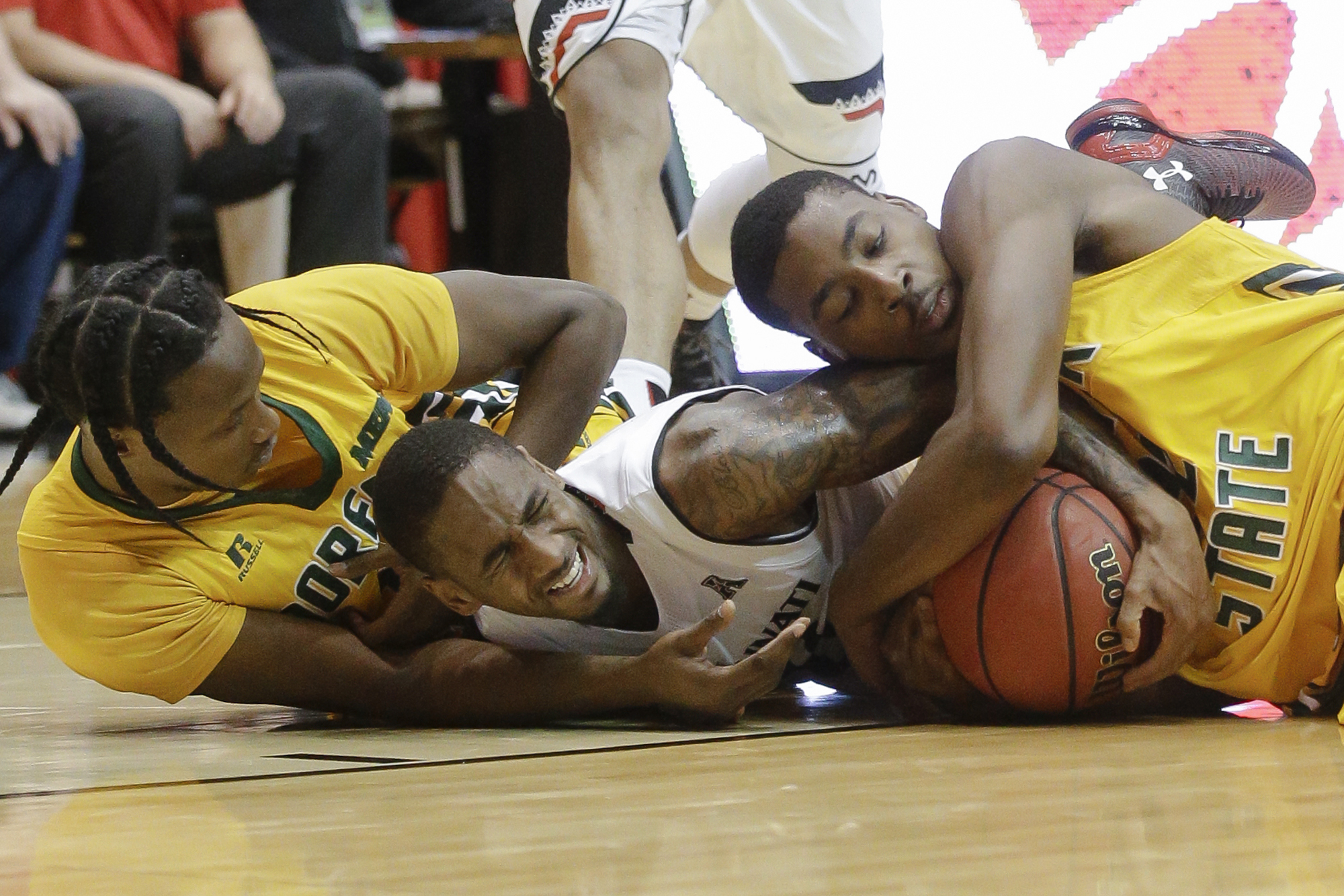 Cincinnati's Farad Cobb, center, scrambles for the ball against Norfolk State's Jeff Short, left, and Alex Long during the first half of an NCAA college basketball game Tuesday, Dec. 15, 2015, in Cincinnati. (AP Photo/John Minchillo)
