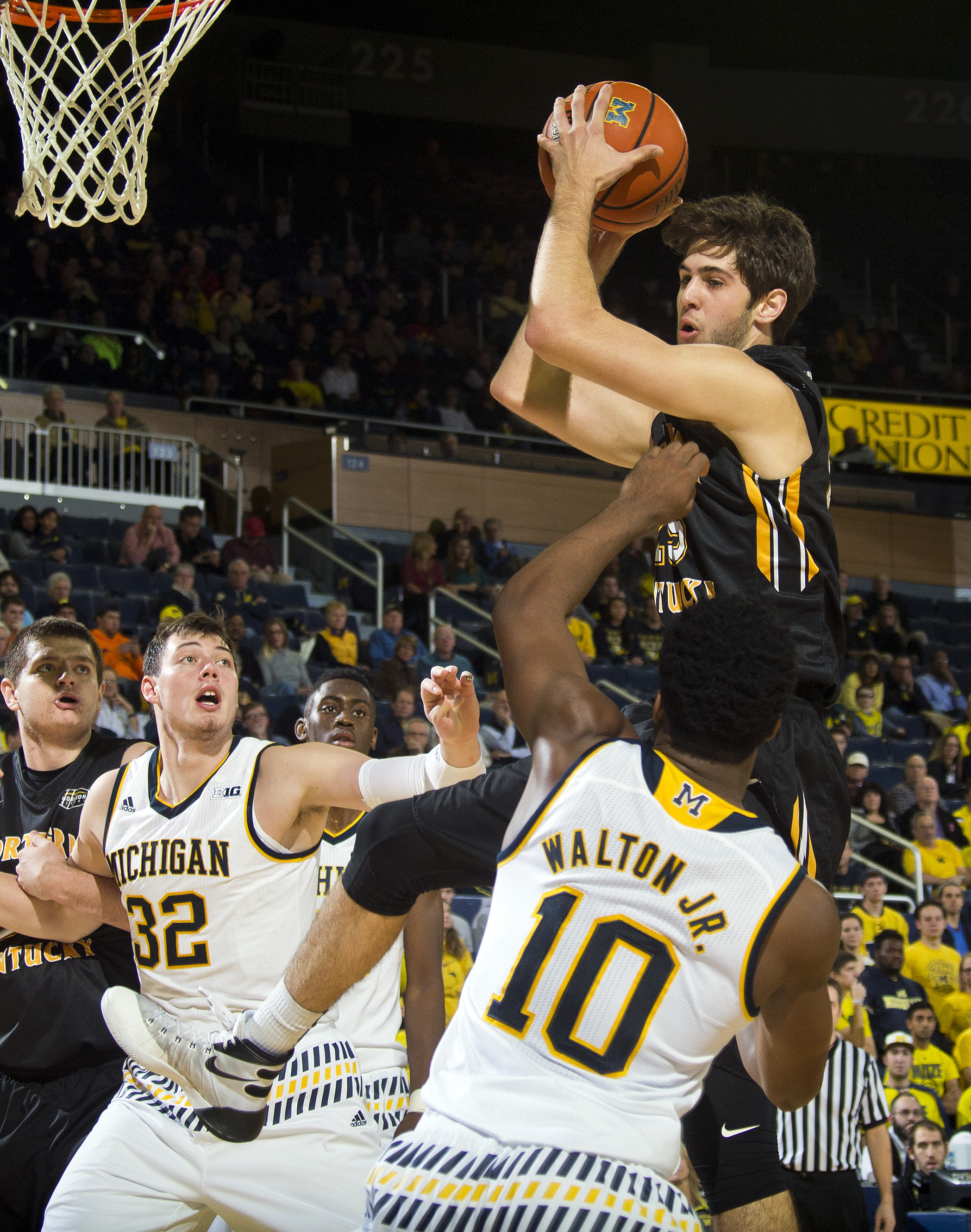 Northern Kentucky guard Cole Murray, top, grabs a rebound above Michigan forward Ricky Doyle (32) and guard Derrick Walton Jr. (10) during the first half of an NCAA college basketball game at Crisler Center in Ann Arbor, Mich., Tuesday, Dec. 15, 2015. (AP