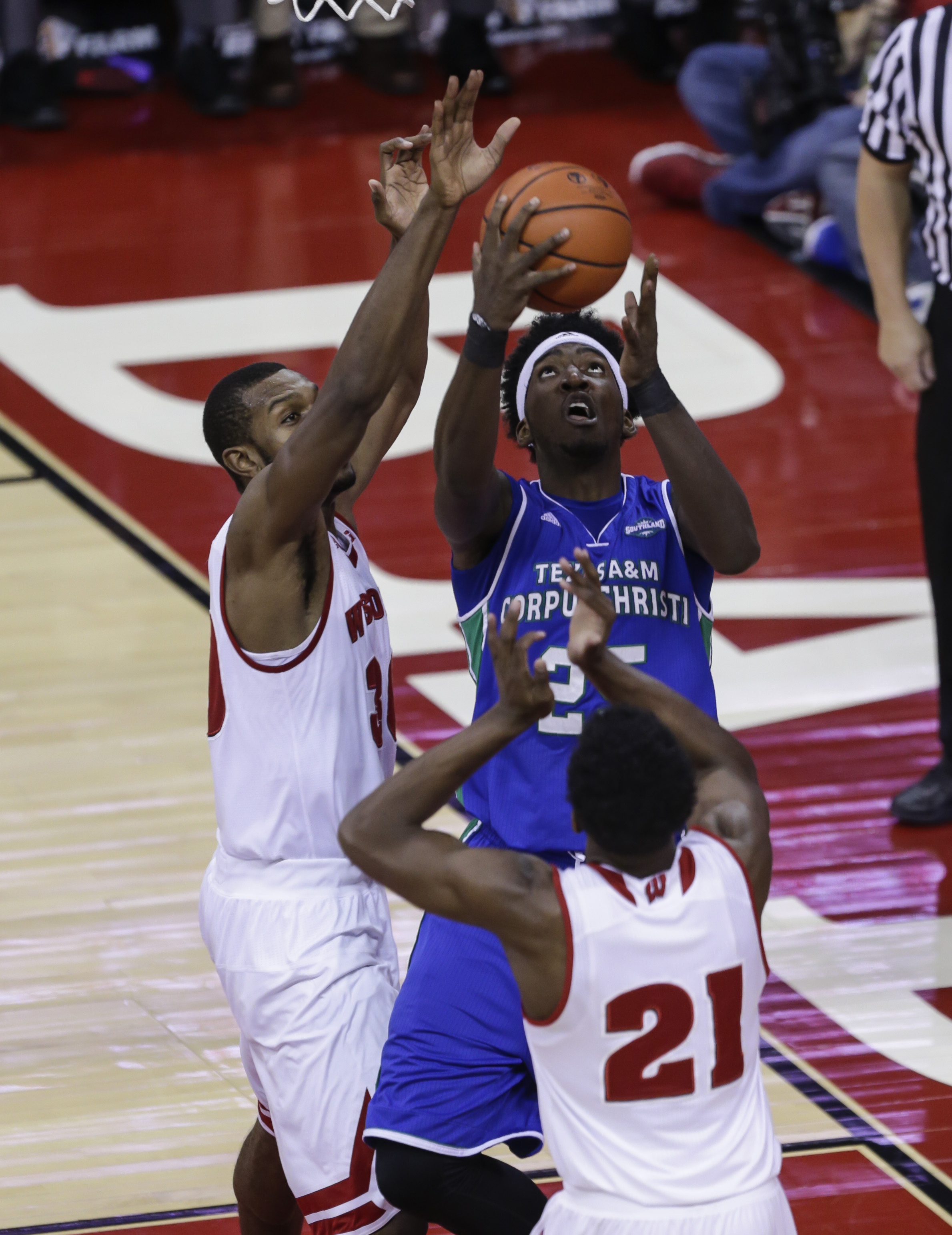 Texas A&M Corpus Christi's Rashawn Thomas (25) shoots against Wisconsin's Vitto Brown, left, and Khalil Iverson (21) during the first half of an NCAA college basketball game Tuesday, Dec. 15, 2015, in Madison, Wis. (AP Photo/Andy Manis)