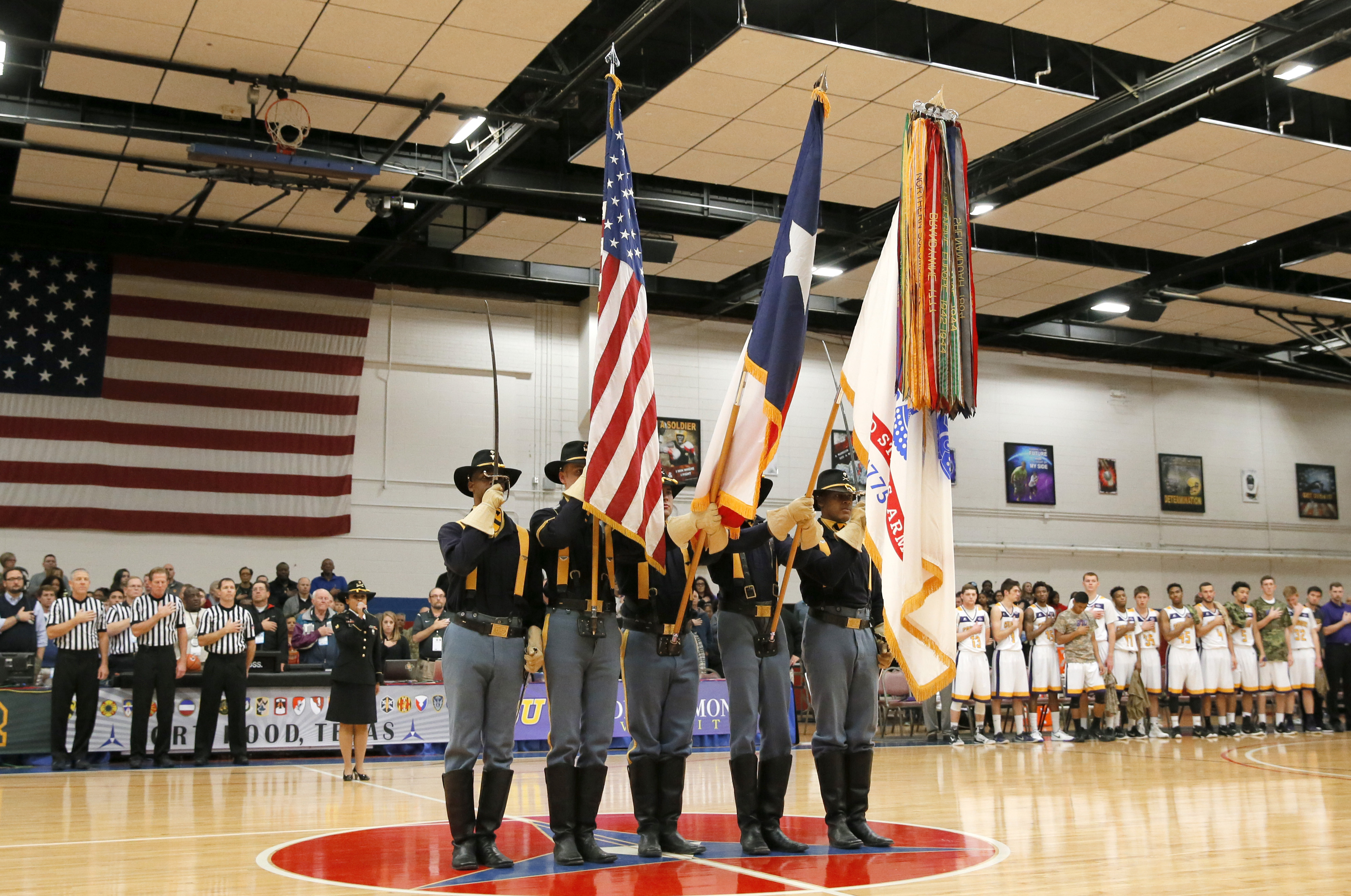Members of the Army's 1st Calvary Division Honor Guard present the colors during the national anthem as members of the Hardin-Simmons basketball team, right rear, watch before an NCAA college basketball game against Baylor on Wednesday, Dec. 16, 2015, at