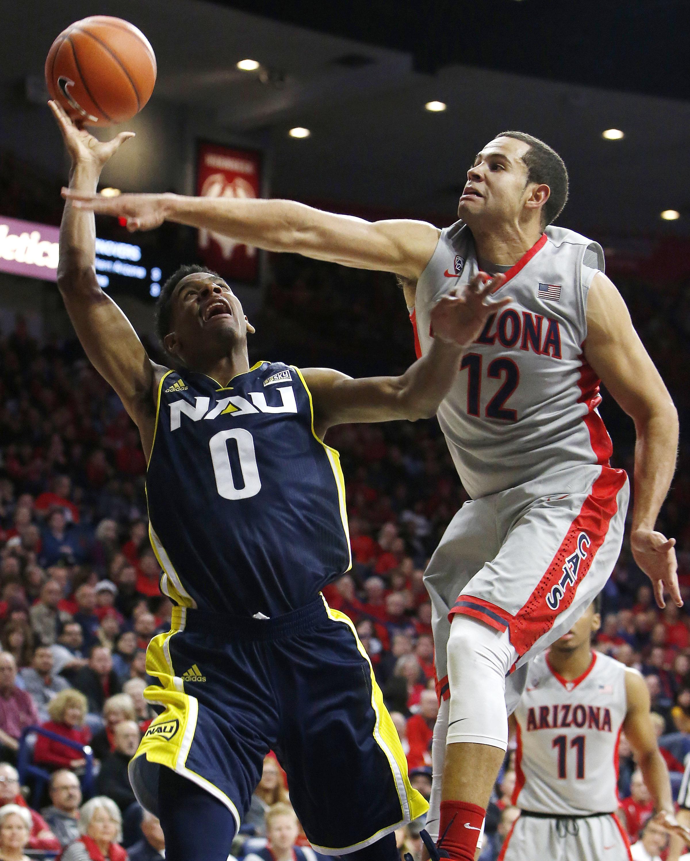 Northern Arizona guard Torry Johnson (0) draws the foul on Arizona forward Ryan Anderson during the first half of an NCAA college basketball game, Wednesday, Dec. 16, 2015, in Tucson, Ariz. (AP Photo/Rick Scuteri)