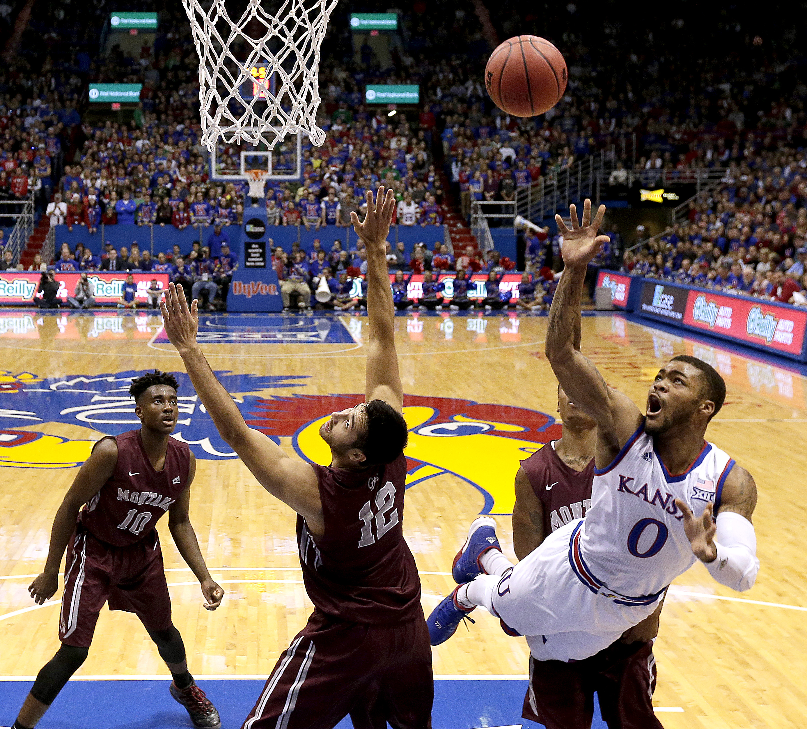 Kansas' Frank Mason III (0) gets past Montana's Martin Breunig (12) to put up a shot during the first half of an NCAA college basketball game Saturday, Dec. 19, 2015, in Lawrence, Kan. (AP Photo/Charlie Riedel)