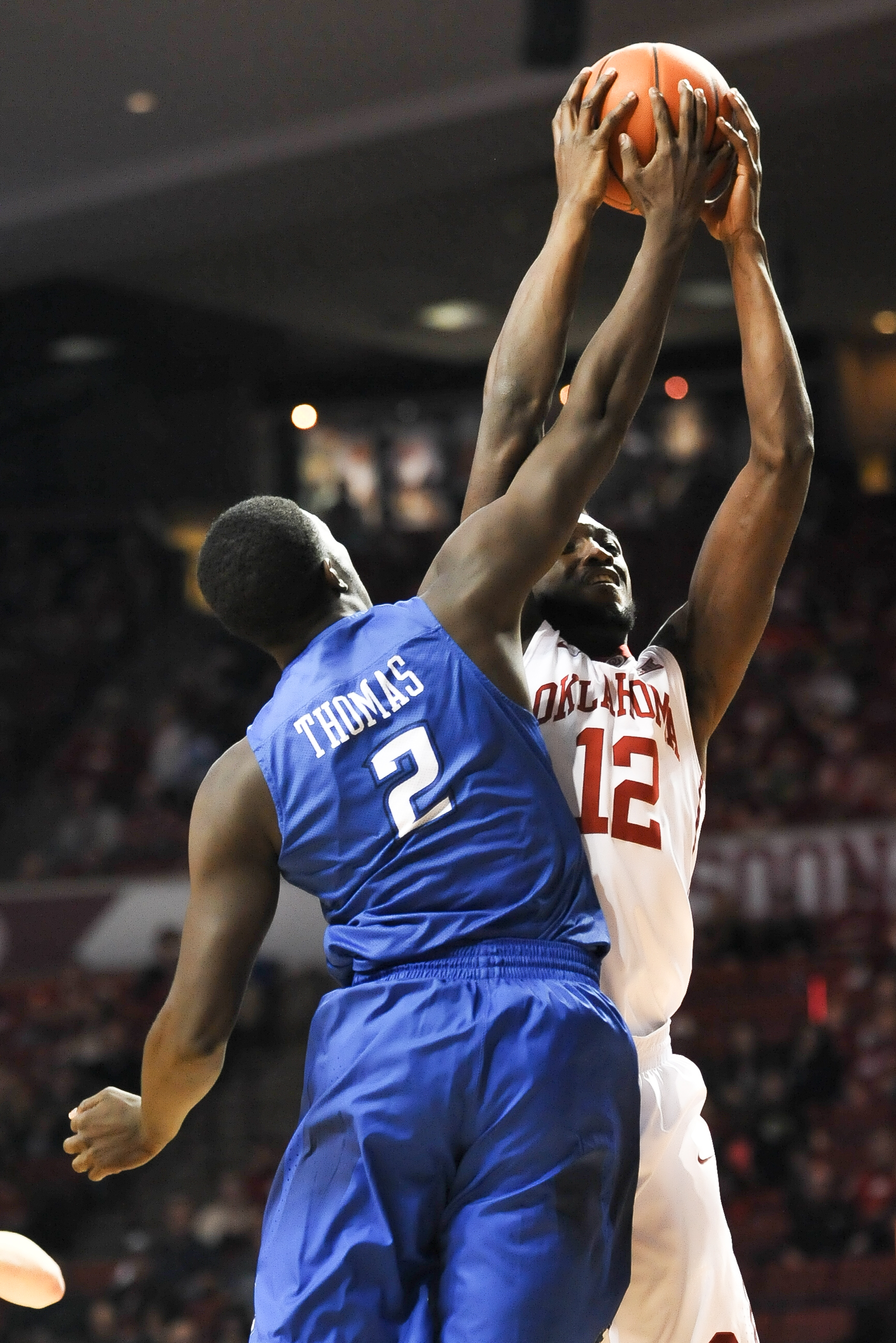 Oklahoma forward Khadeem Lattin (12) grabs a rebound over Creighton guard Khyri Thomas (2) during the first half of an NCAA basketball game in Norman, Okla., Saturday, Dec. 19, 2015. (AP Photo/Kyle Phillips)