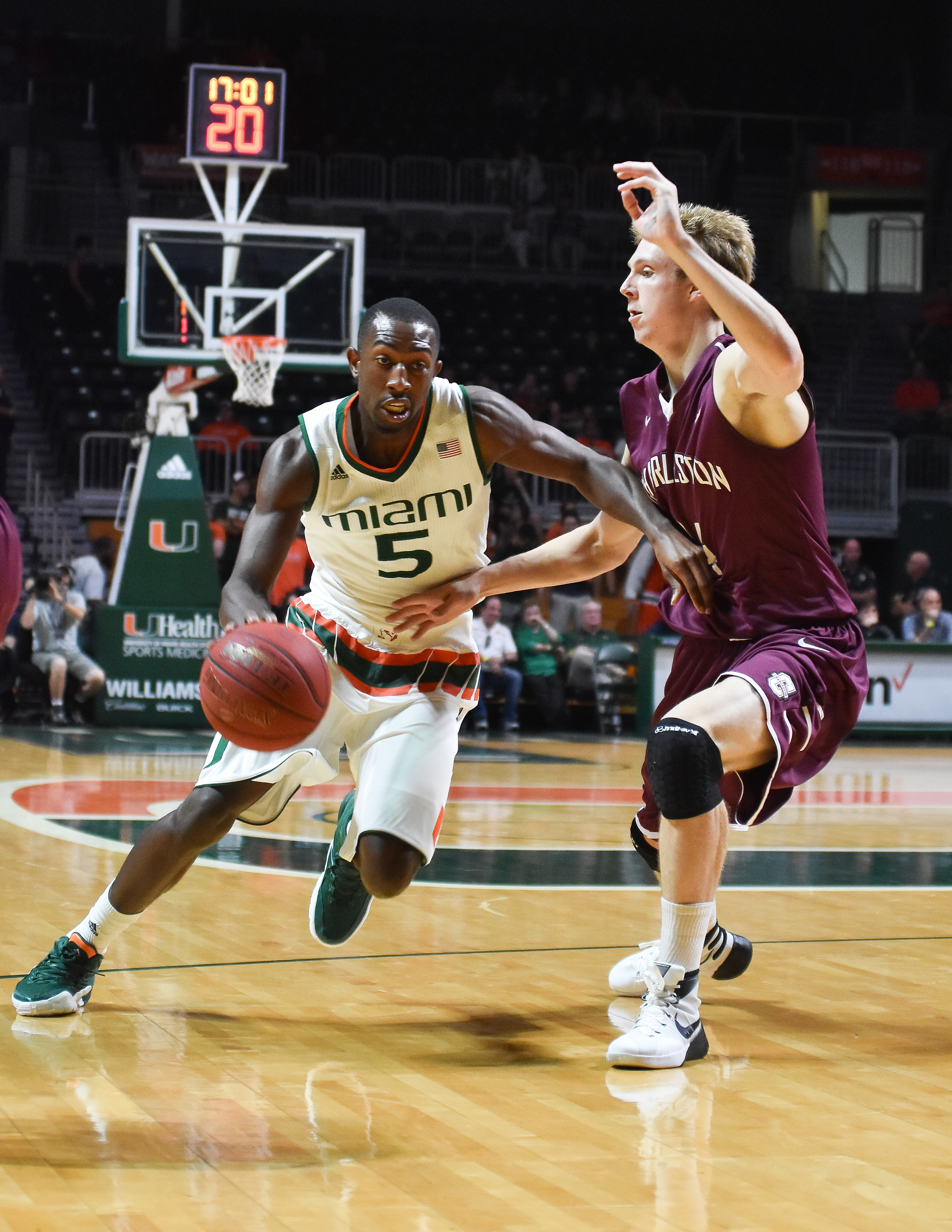 Miami guard Anthony Lawrence Jr. attempts to get by Charleston's Canyon Barry during first half of an NCAA college basketball game in Coral Gables, Fla., Saturday, Dec. 19, 2015. (AP Photo/Gaston De Cardenas)