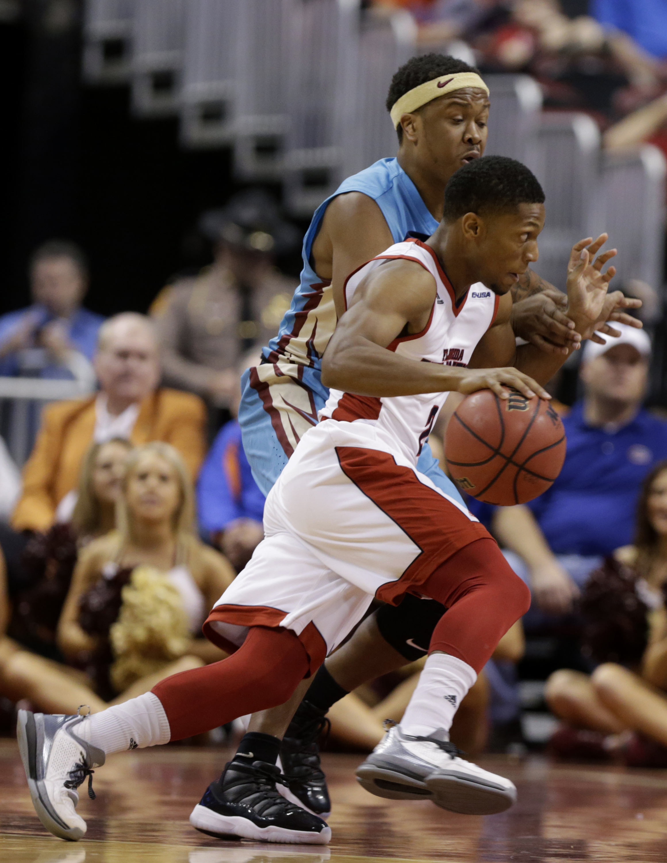 Florida Atlantic's Marquan Botley, right, drives to the basket as Florida State 's Benji Bell, left, defends in the first half of the NCAA college Orange Bowl Basketball Classic, Saturday, Dec. 19, 2015, in Sunrise, Fla. (AP Photo/Lynne Sladky)