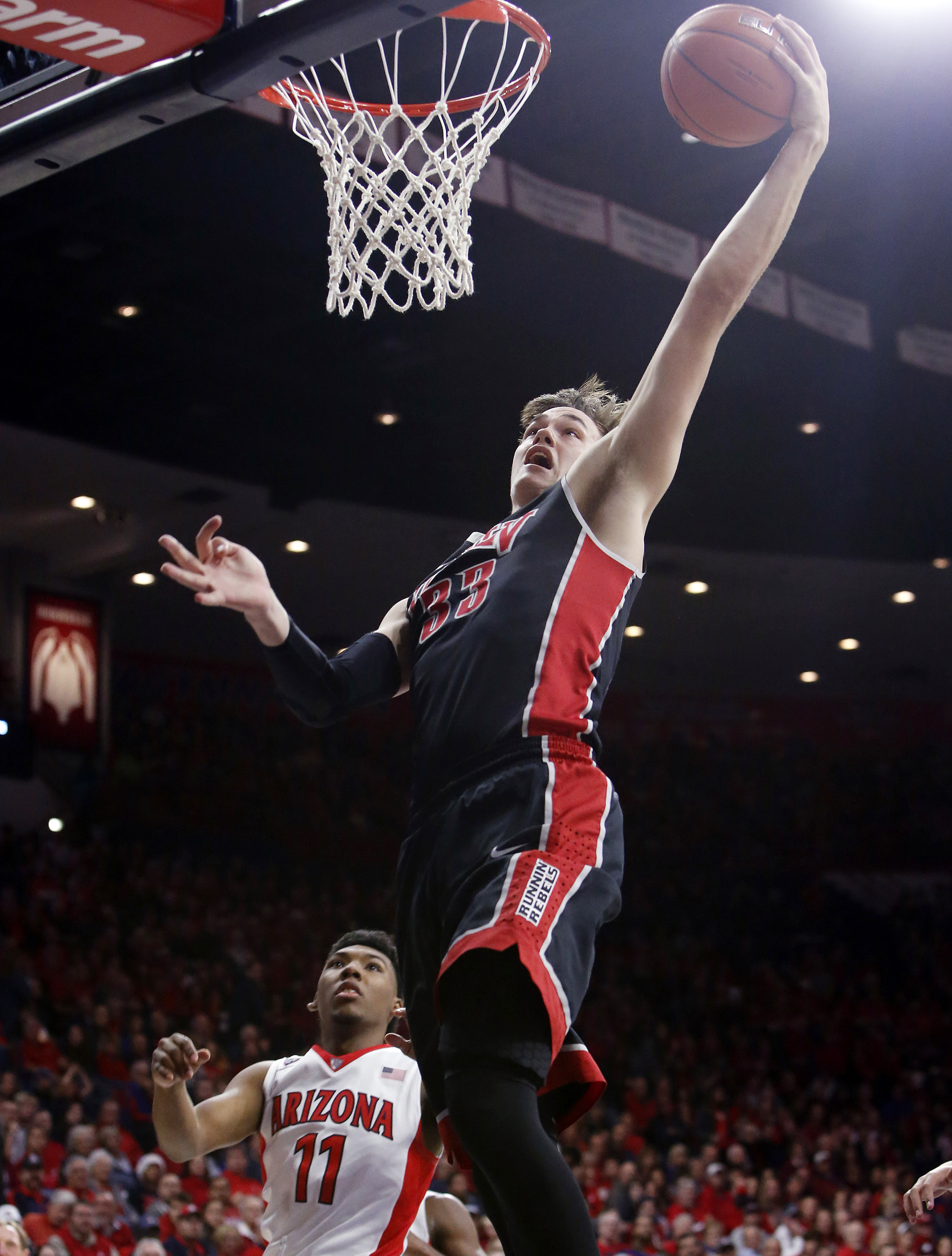 UNLV forward Stephen Zimmerman Jr. (33) drives past Arizona guard Allonzo Trier during the first half of an NCAA college basketball game Saturday, Dec. 19, 2015, in Tucson, Ariz. (AP Photo/Rick Scuteri)