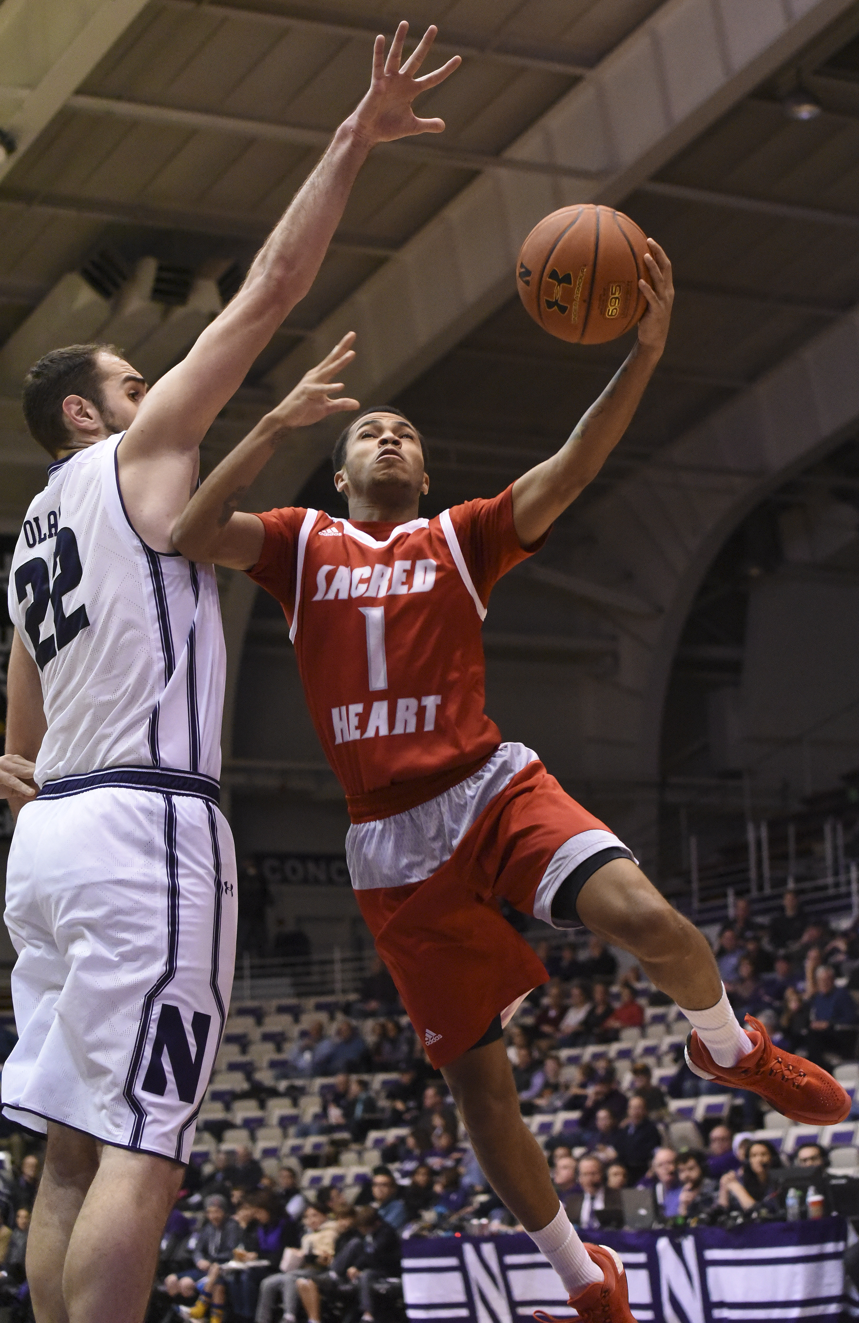 Sacred Heart guard Cane Broome (1) is defended by Northwestern center Alex Olah (22) during the first half of an NCAA college basketball game Monday, Dec. 21, 2015, in Evanston Ill. (AP Photo/David Banks)