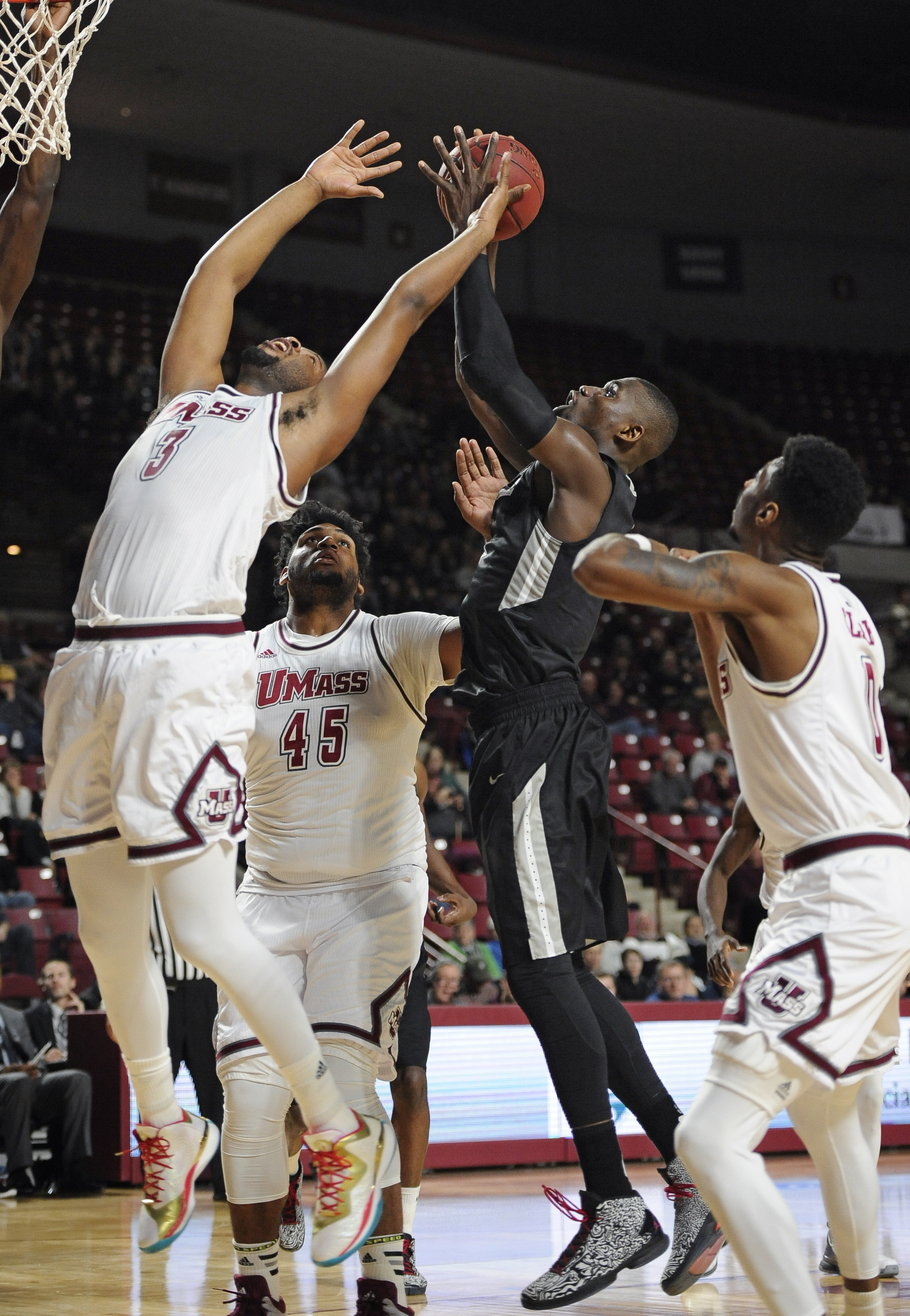 Providence's Ben Bentil, center shoots past Massachusetts' Jabarie Hinds, left, Rashaan Holloway, center, and Donte Clark, right, in the second half of an NCAA college basketball game, Monday, Dec. 21, 2015, in Amherst, Mass. Providence won 90-66.  (AP Ph