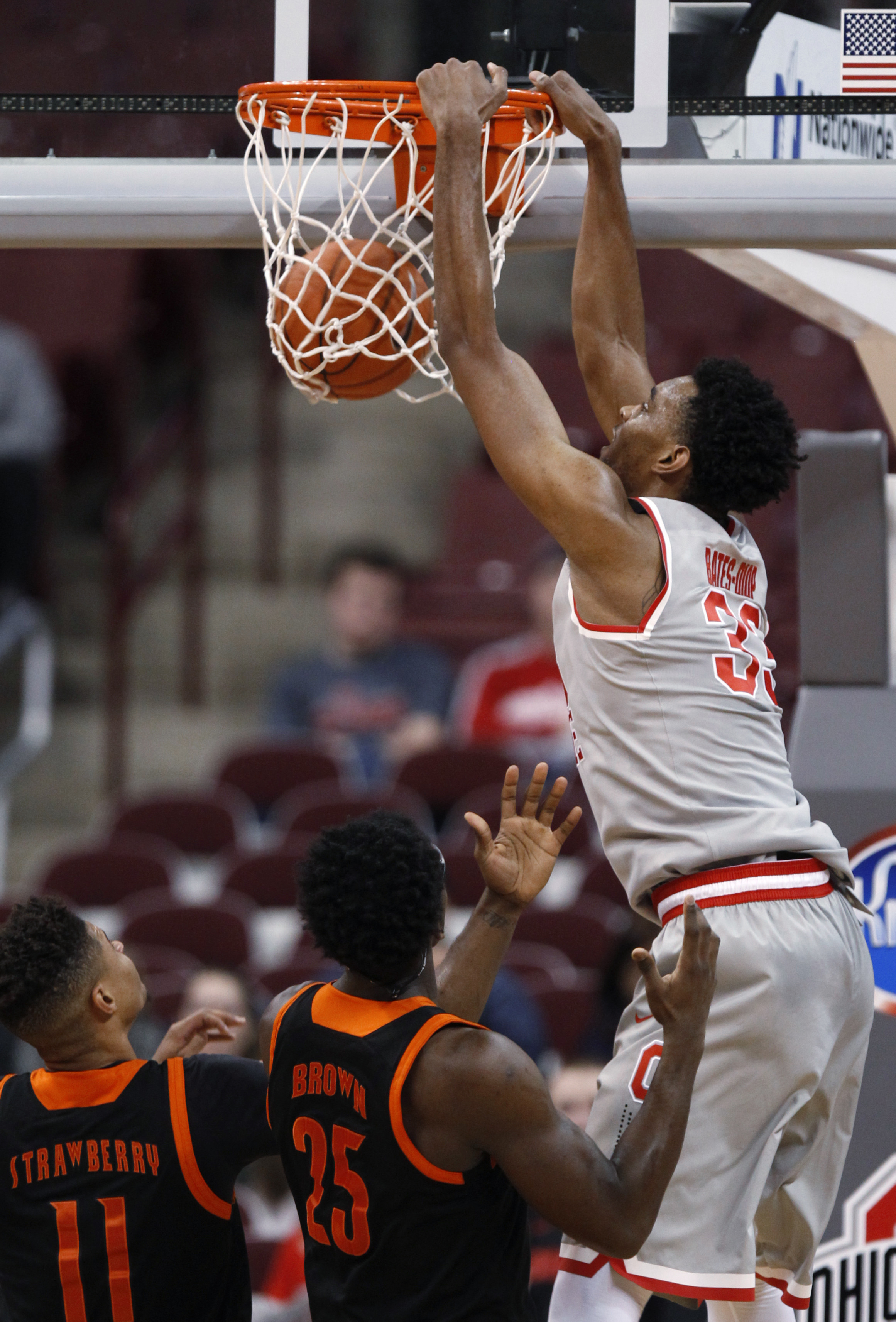 Ohio State's Keita Bates-Diop, right, dunks the ball against Mercer's Jordan Strawberry (11) and Lawrence Brown (25) during the first half of an NCAA college basketball game in Columbus, Ohio, Tuesday, Dec. 22, 2015. (AP Photo/Paul Vernon)