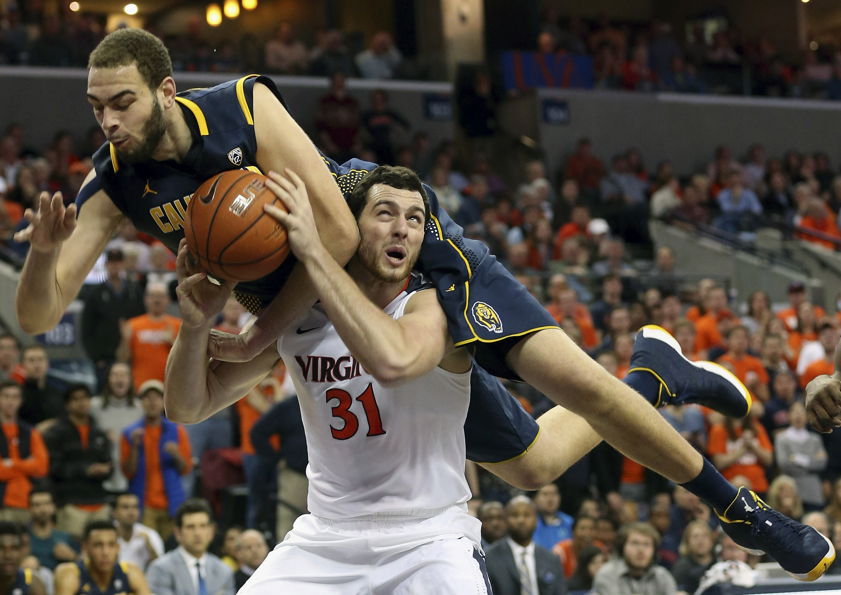 Virginia forward Jarred Reuter (31) gets fouled by California center Kameron Rooks during an NCAA basketball game Tuesday Dec. 22, 2015, in Charlottesville, Va. (AP Photo/Andrew Shurtleff)