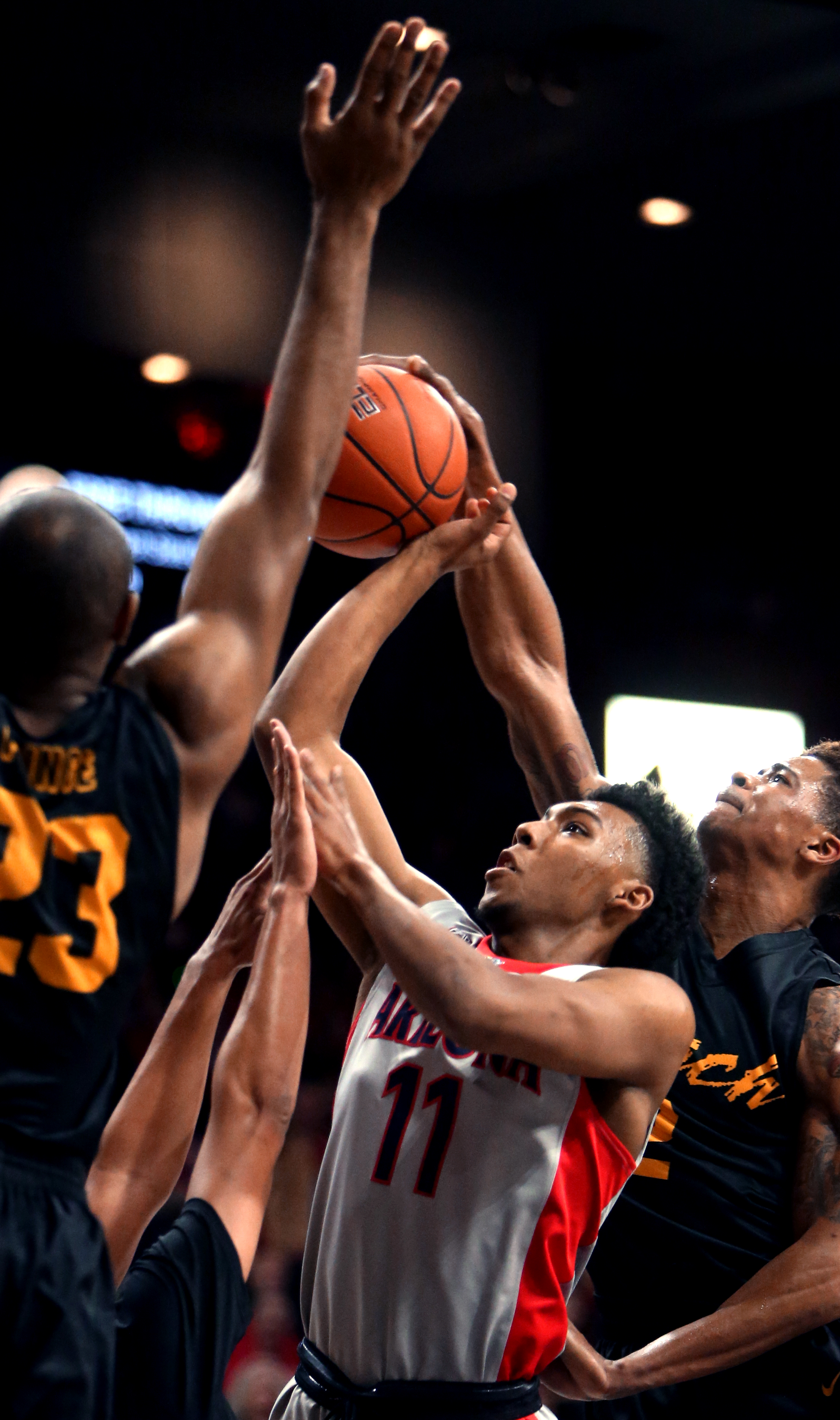 Arizona guard Allonzo Trier (11) drives into the lane between Long Beach State forward Roschon Prince, left, guard A.J. Spencer (15) and guard Nick Faust (2) during the first half of an NCAA college basketball game Tuesday, Dec. 22, 2015, in Tucson, Aria.