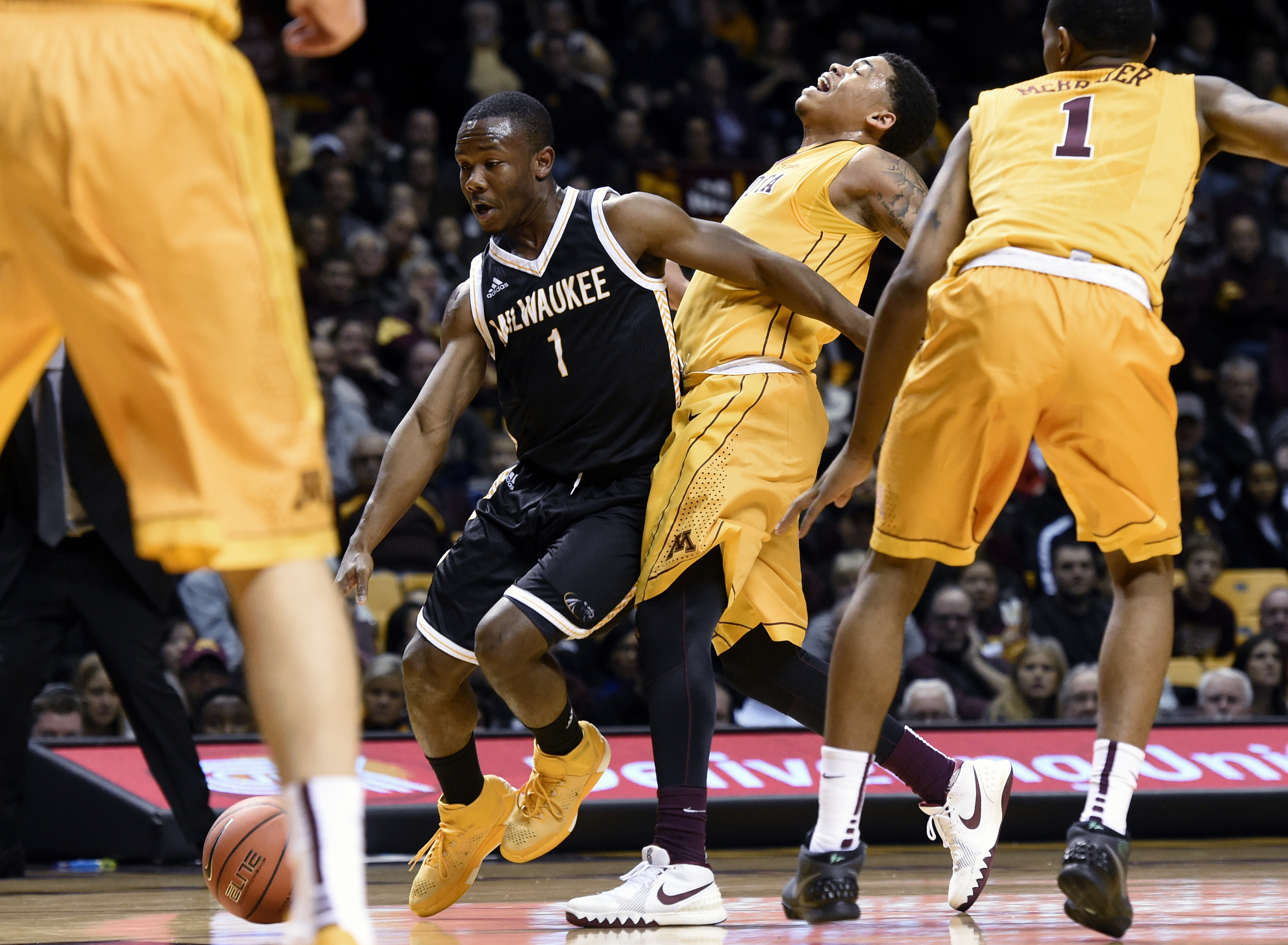 Milwaukee guard Jordan Johnson (1) is called for an offensive foul on Minnesota guard Nate Mason (2) as Minnesota guard Dupree McBrayer (1) watches during the first half of an NCAA college basketball game Wednesday, Dec. 23, 2015, in Minneapolis. (AP Phot