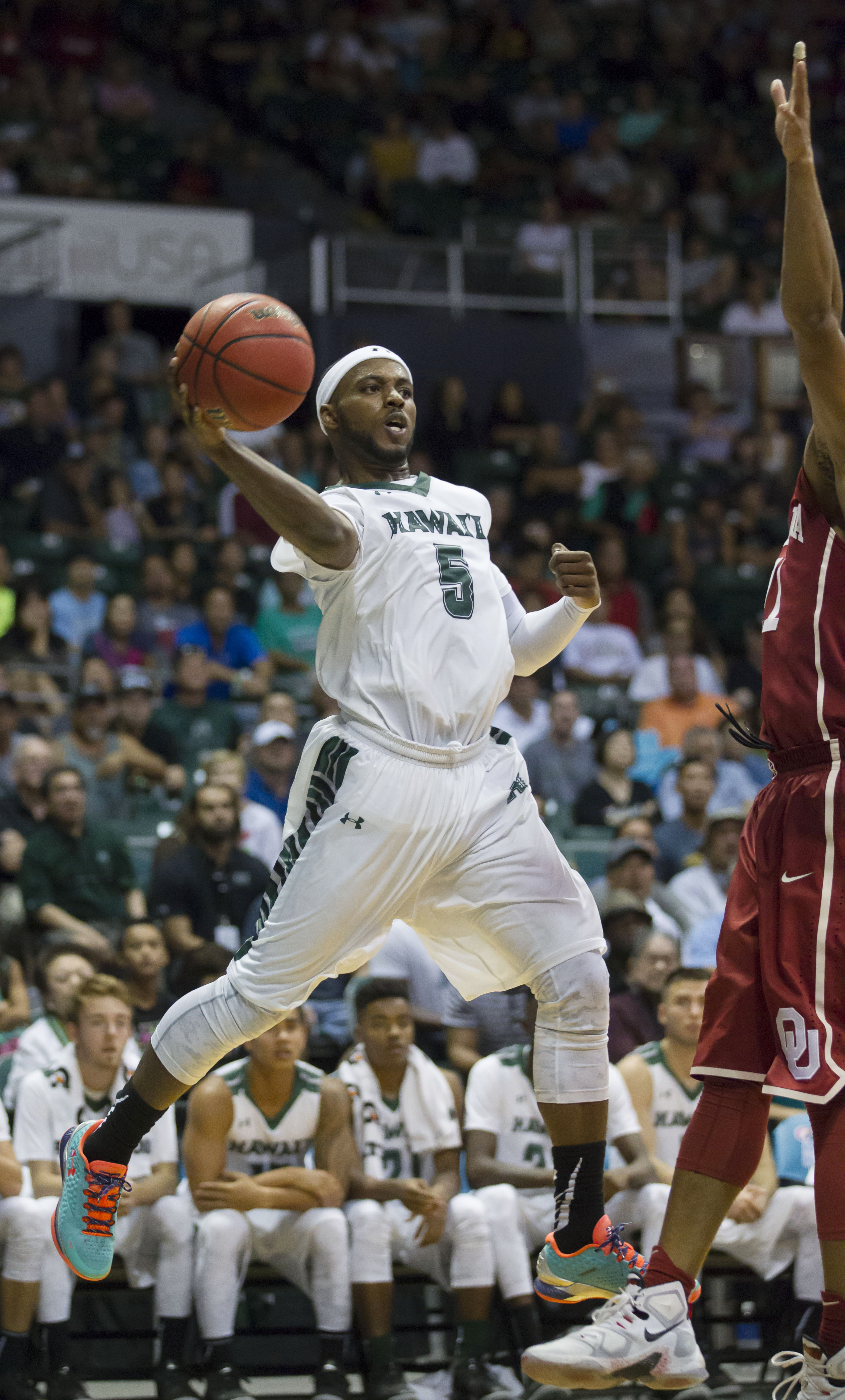 Hawaii guard Roderick Bobbitt drives the baseline then passes off to a teammate as  Oklahoma guard Isaiah Cousins, right, defends during the second half of an NCAA college basketball game at the Diamond Head Classic, Wednesday, Dec. 23, 2015, in Honolulu.
