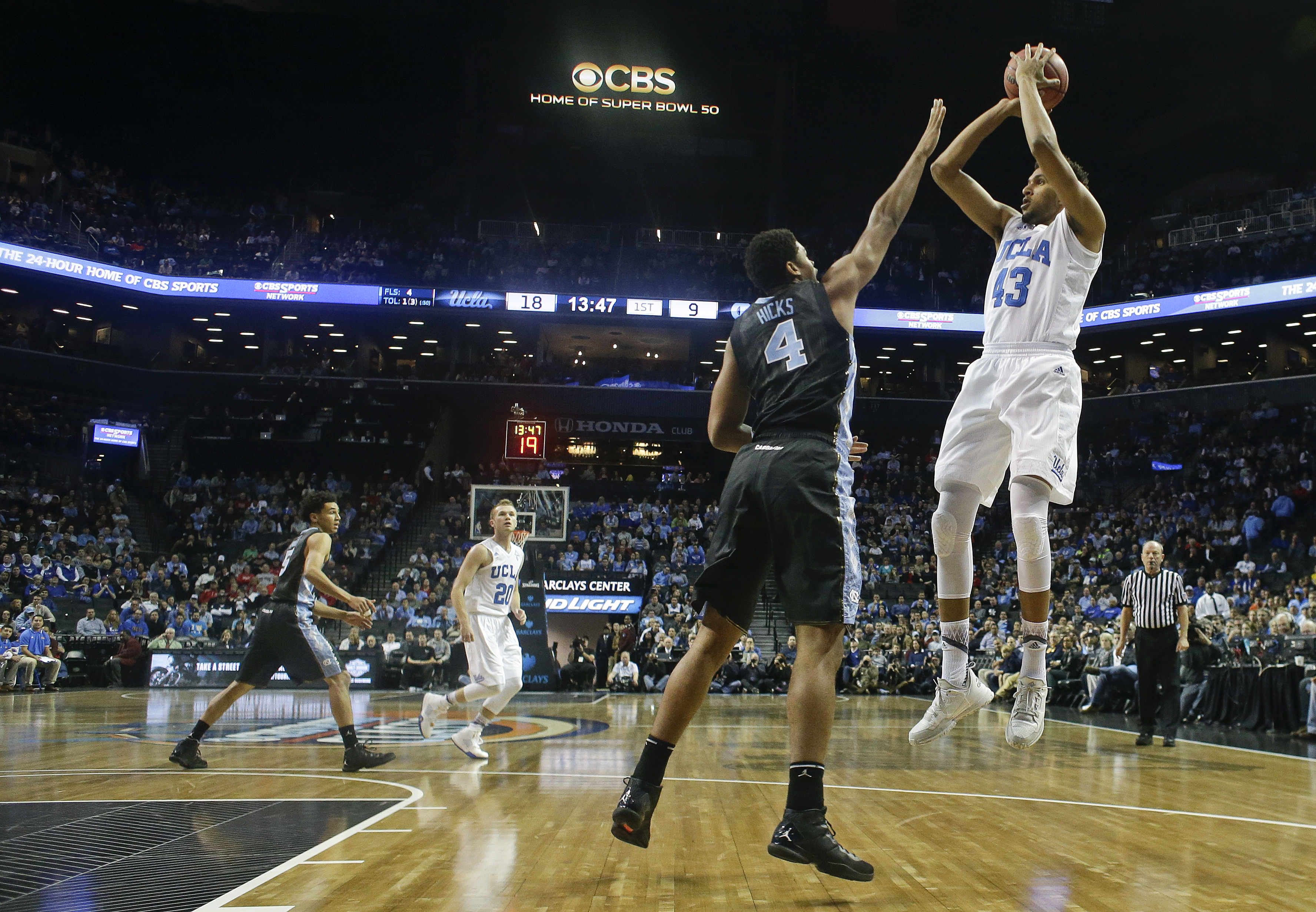FILE - In this Dec. 19, 2015, file photo, UCLA's Jonah Bolden (43) shoots over North Carolina's Isaiah Hicks (4) during the first half of an NCAA college basketball game in New York. Shorter shot clocks and fewer timeouts. Less hand-checking and physical