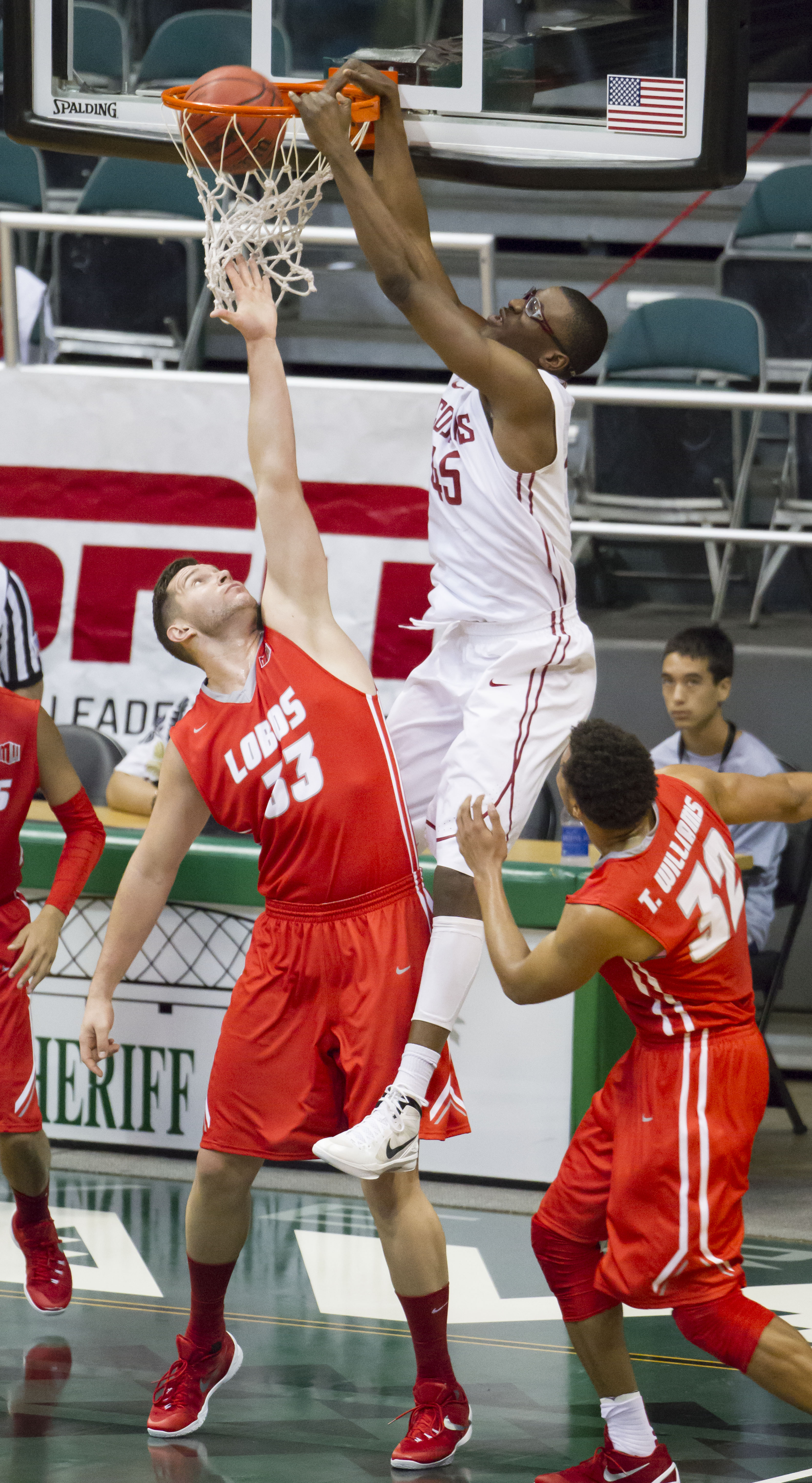 Washington State center Valentine Izundu, right, dunks over New Mexico center Nikola Scekic (33) as forward Tim Williams (32) looks on in the first half of an NCAA college basketball game at the Diamond Head Classic, Friday, Dec. 25, 2015, in Honolulu. (A