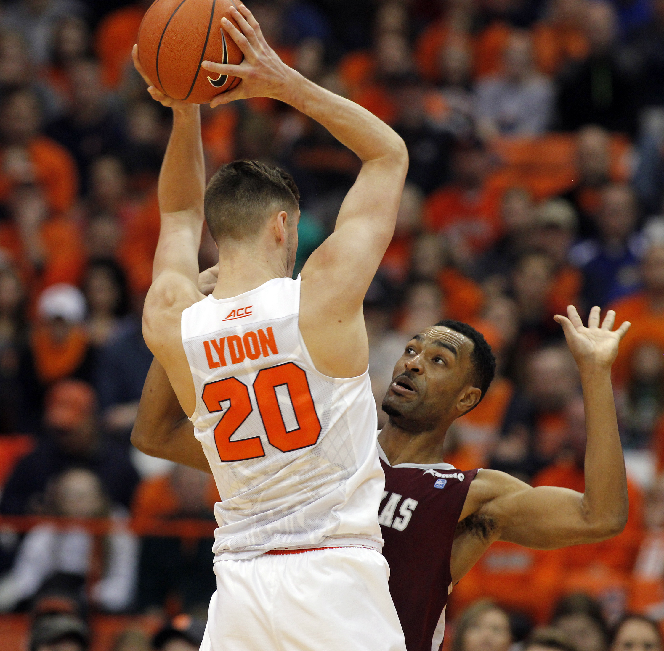 Syracuse's Tyler Lydon, left, looks to pass the ball under pressure from Texas Southern's Malcolm Riley, right, in the first half of an NCAA college basketball game in Syracuse, N.Y., Sunday, Dec. 27, 2015. (AP Photo/Nick Lisi)