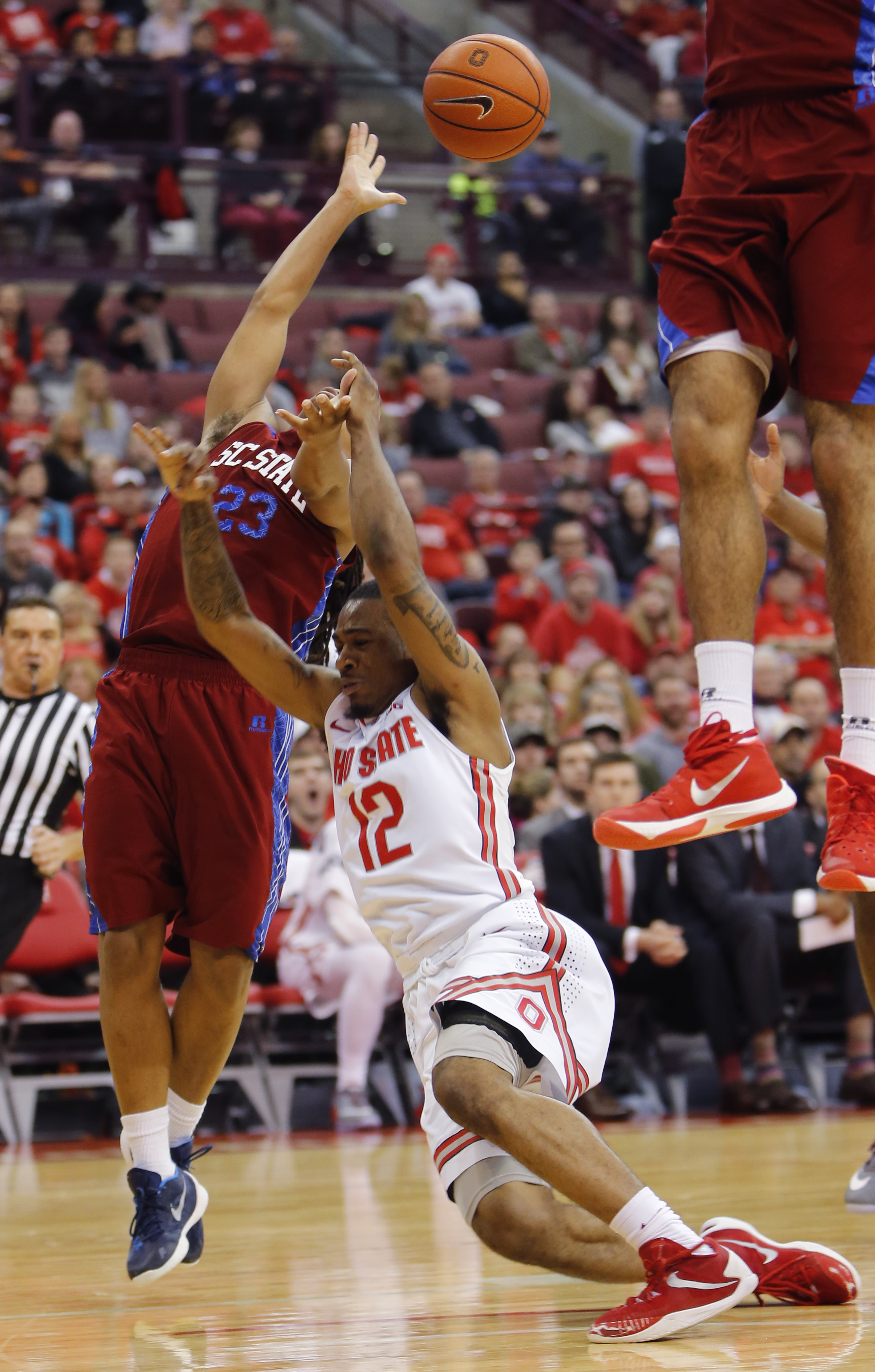 South Carolina State's Ty Soloman, left, fouls Ohio State's A.J. Harris as he tries to shoot during the second half of an NCAA college basketball game Sunday, Dec. 27, 2015, in Columbus, Ohio. Ohio State beat South Carolina State 73-57. (AP Photo/Jay LaPr
