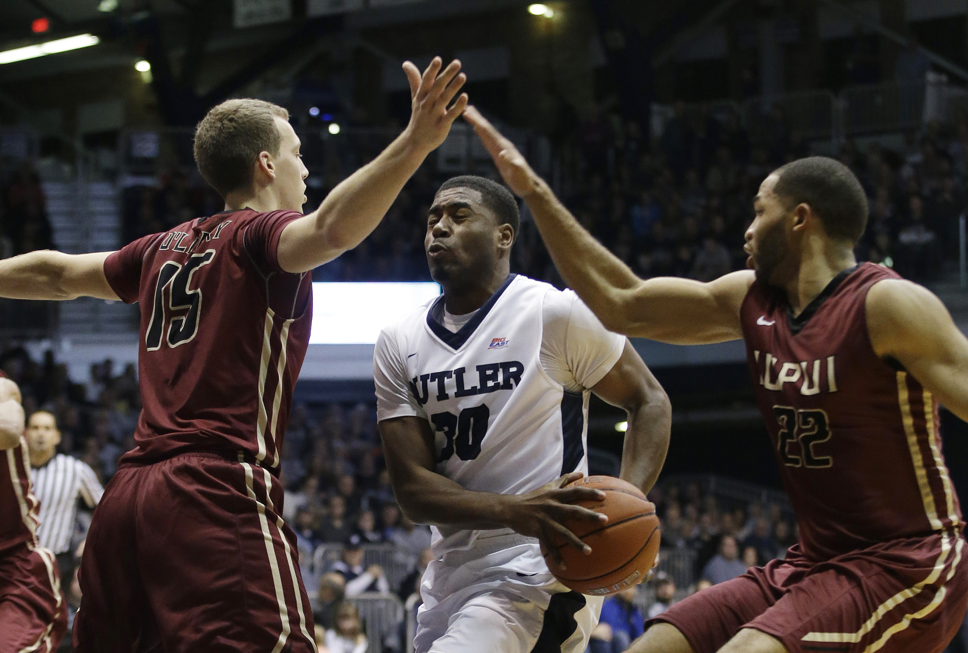 Butler's Kelan Martin (30) goes to the basket against IUPUI's Matt O'Leary (15) and Marcellus Barksdale (22) during the first half of an NCAA college basketball game Monday, Dec. 28, 2015, in Indianapolis. (AP Photo/Darron Cummings)
