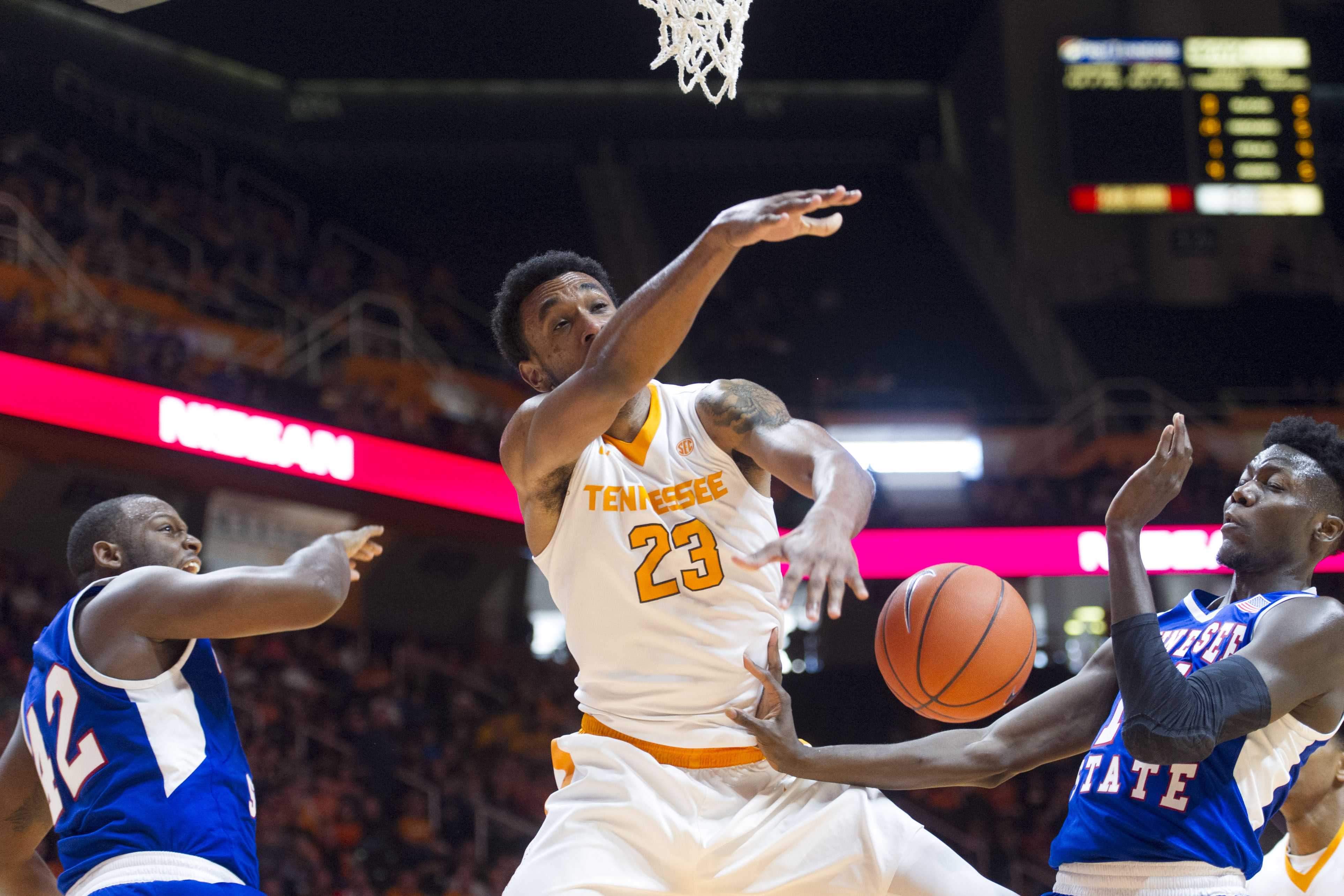 Tennessee's Derek Reese (23) is fouled while trying to score between Tennessee State's Christian Griggs-Williams, left, and Demontez Loman during the first half of an NCAA college basketball game in Knoxville, Tenn., on Tuesday, Dec. 29, 2015.  Tennessee