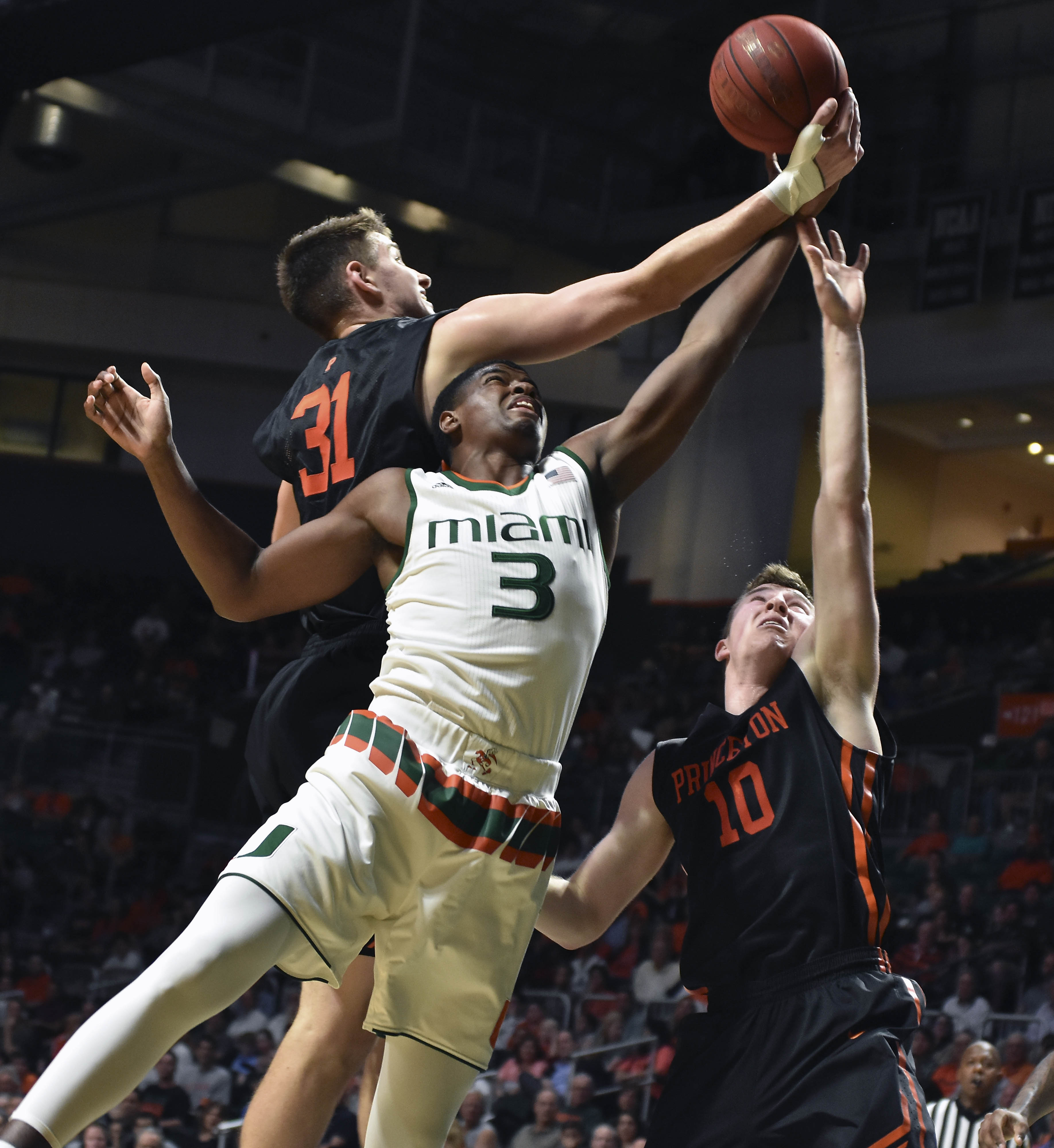 Miami guard Anthony Lawernce, Jr. goes up for a lay up against Princeton's Pete Miller and Spencer Weisz during the first half of an NCAA college basketball game at the Bank United Center in Coral Gables, Fla., Tuesday,  Dec. 29, 2015. (AP Photo/Gaston De