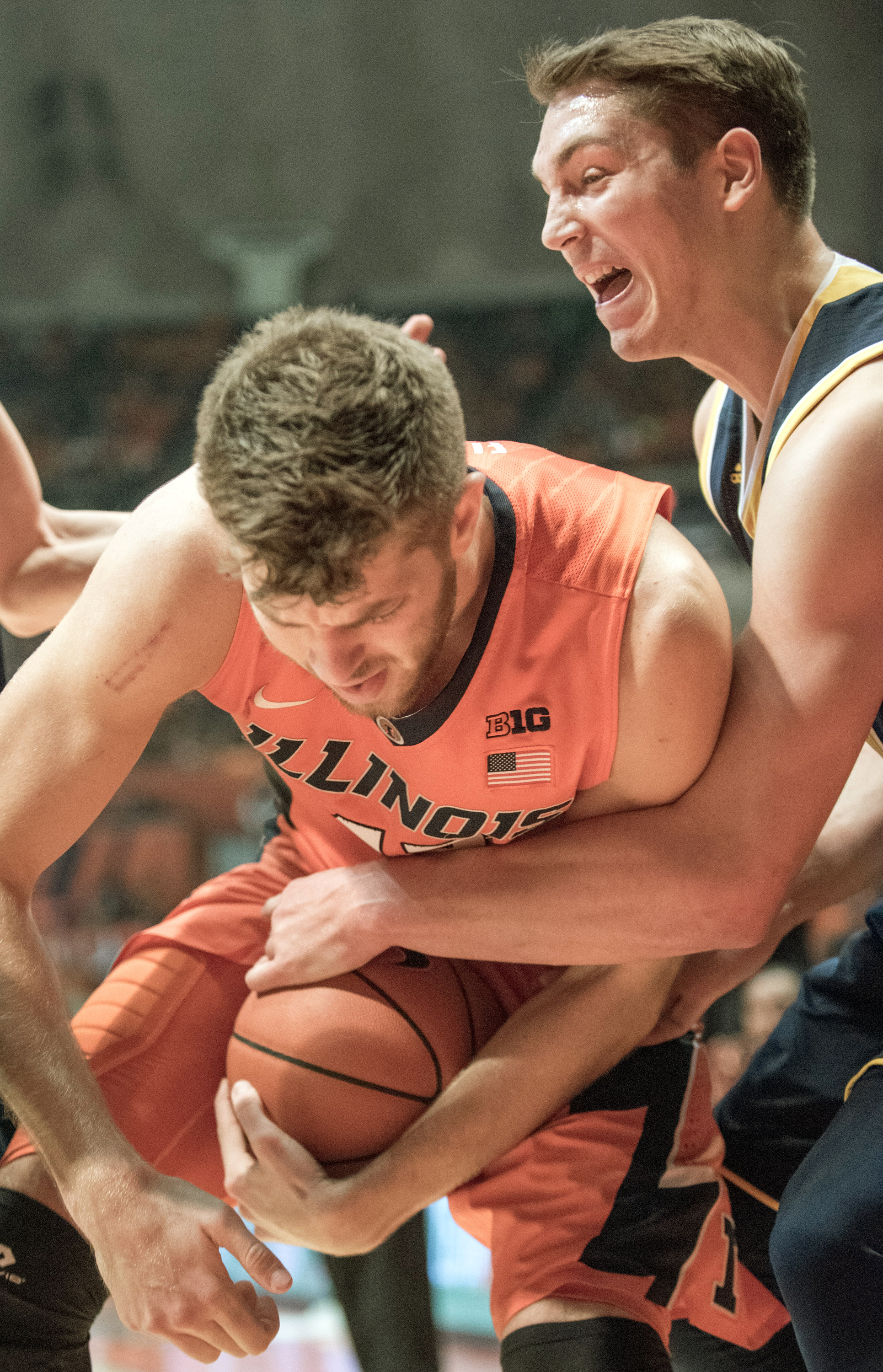 Illinois forward Michael Finke (43) and Michigan's forward Mark Donnal (34) vie for the ball during the first half of an NCAA  college basketball game, Wednesday, Dec. 30, 2015, in Champaign, Ill. (AP Photo/Robin Scholz)