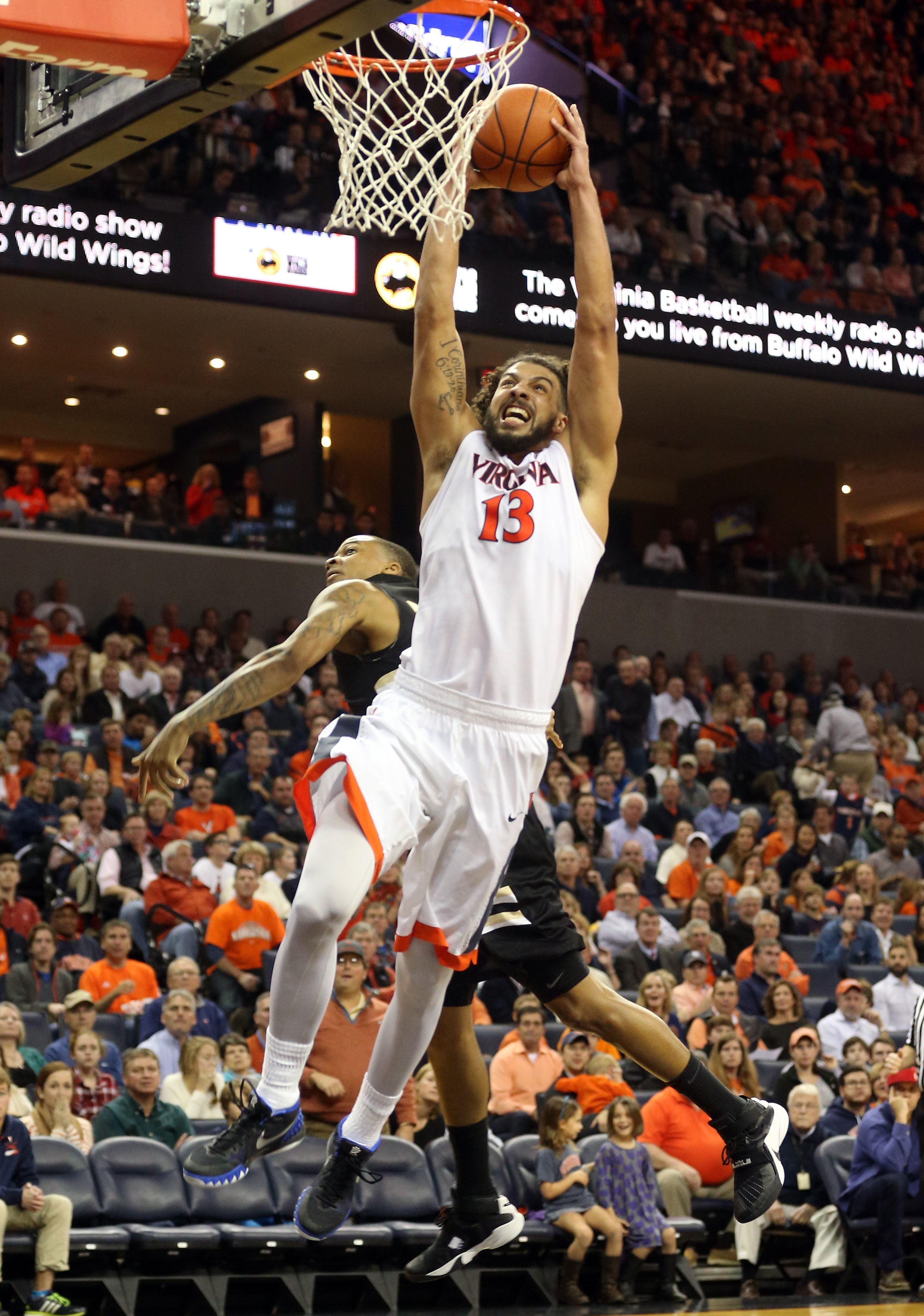 Virginia forward Anthony Gill (13) dunks in front of Oakland guard Sherron Dorsey-Walker (30) during an NCAA basketball game Wednesday Dec. 30, 2015, in Charlottesville, Va. Virginia won 71-58. (AP Photo/Andrew Shurtleff)