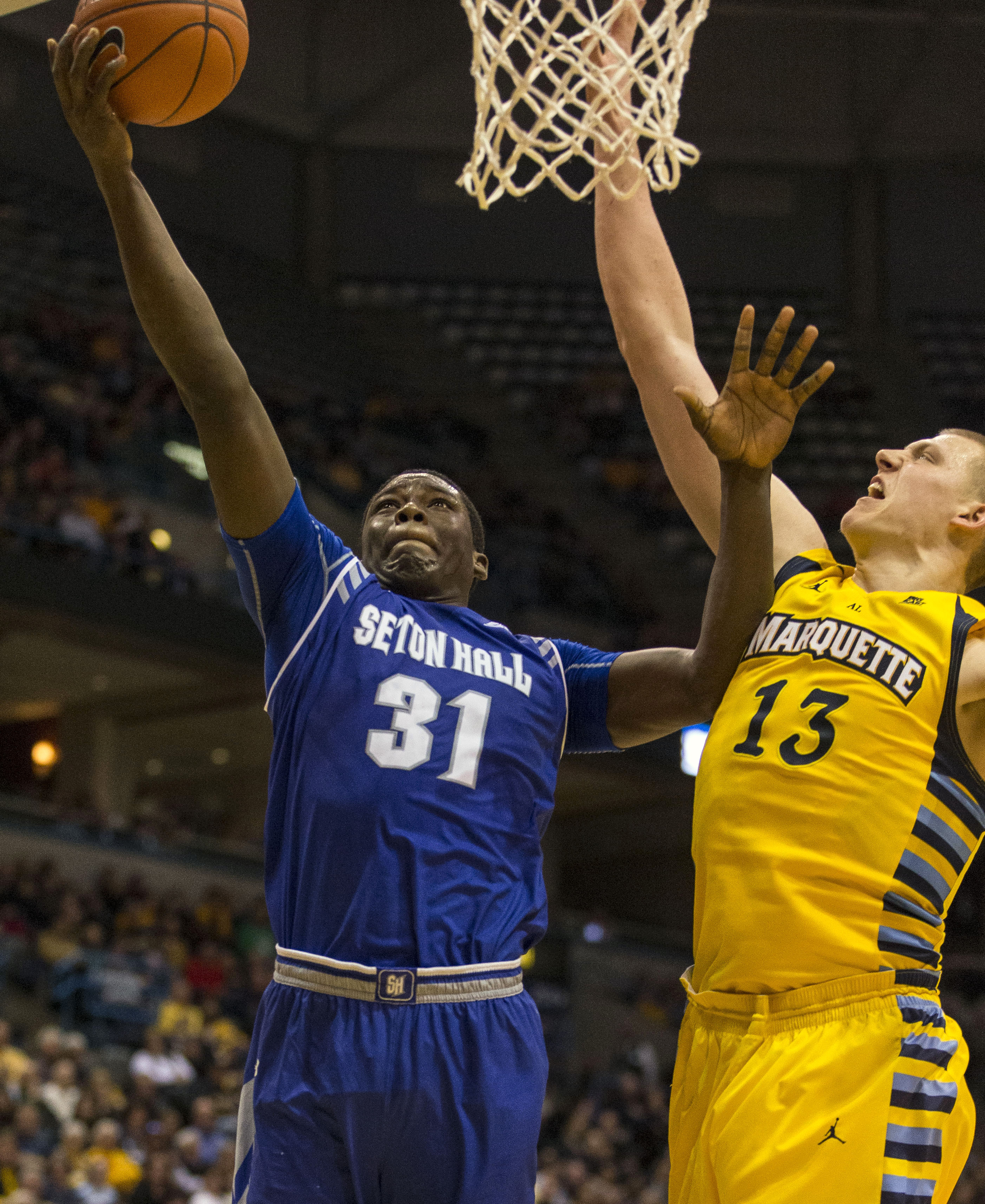 Seton Hall's Angel Delgado (31) shoots as Marquette's Henry Ellenson defends during the second half of an NCAA college basketball game Wednesday, Dec. 30, 2015, in Milwaukee. (AP Photo/Tom Lynn)