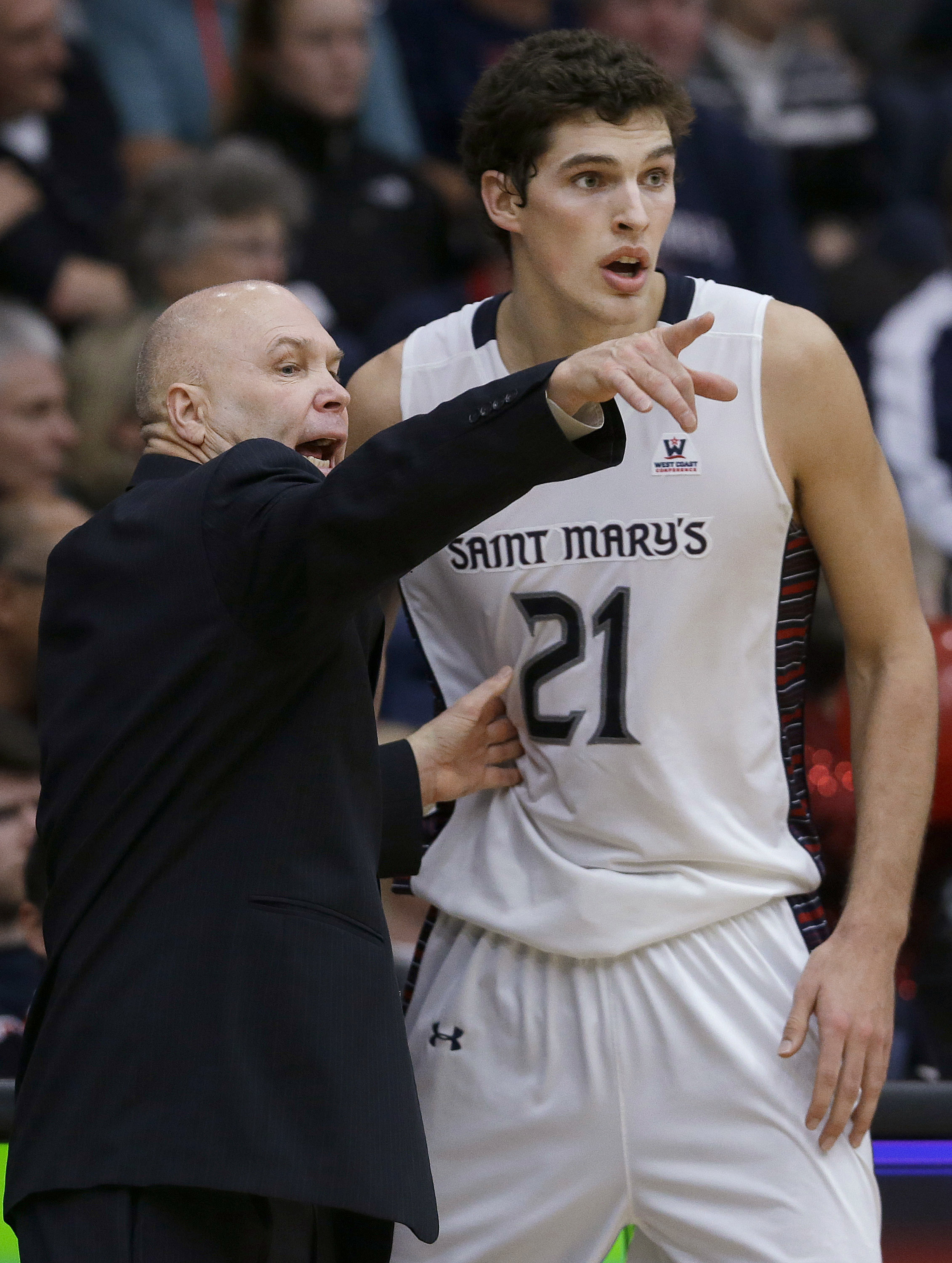 Saint Mary's (Calif.) coach Randy Bennett talks with center Evan Fitzner during the second half of an NCAA college basketball game against BYU in Moraga, Calif., Thursday, Dec. 31, 2015. Saint Mary's won 85-74. (AP Photo/Jeff Chiu)