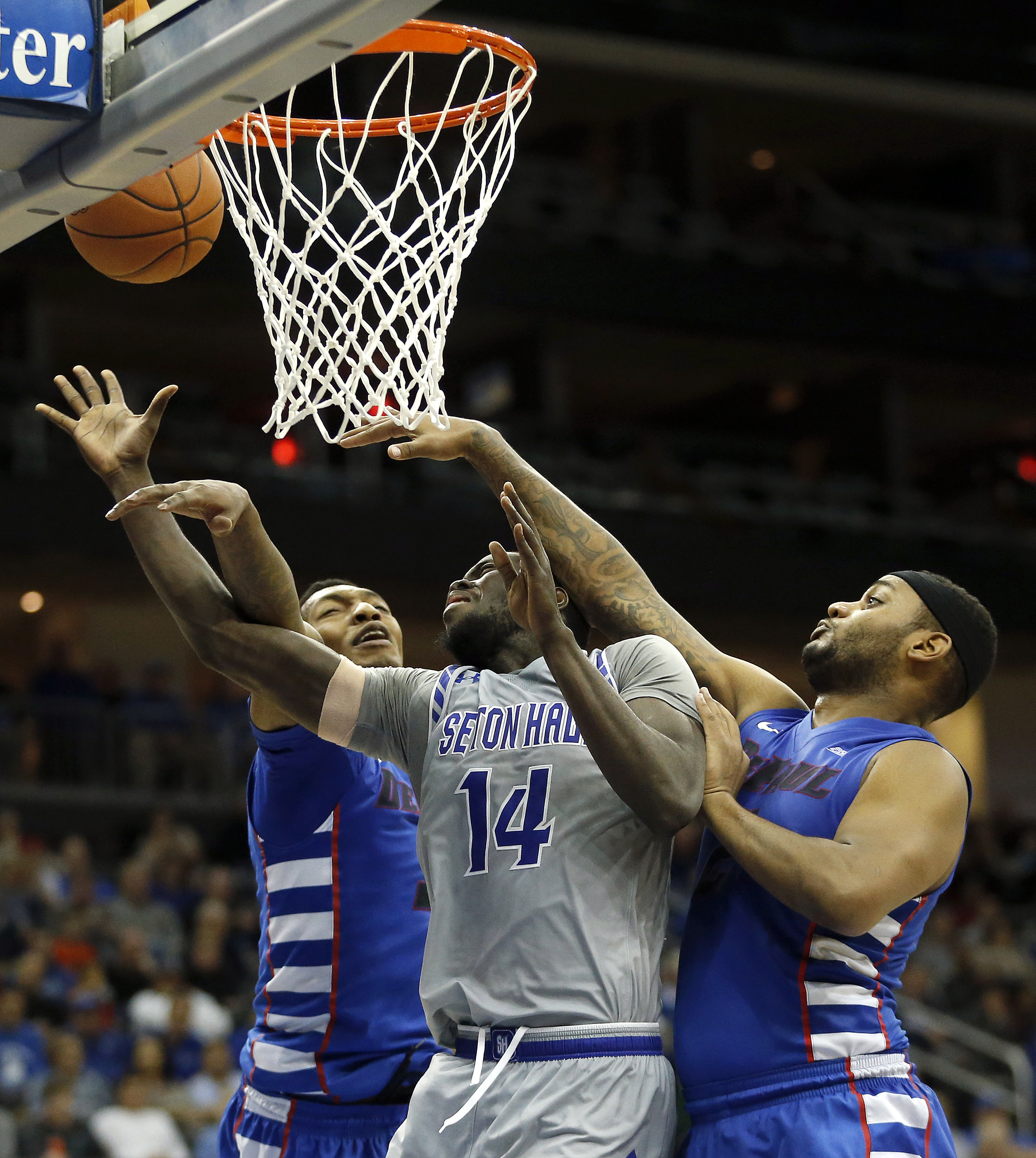 Seton Hall guard Ismael Sanogo (14) is fouled while going up for a shot against DePaul forward Rashaun Stimage, left, and center Tommy Hamilton IV during the second half of an NCAA college basketball game, Saturday, Jan. 2, 2016, in Newark, N.J. Seton Hal