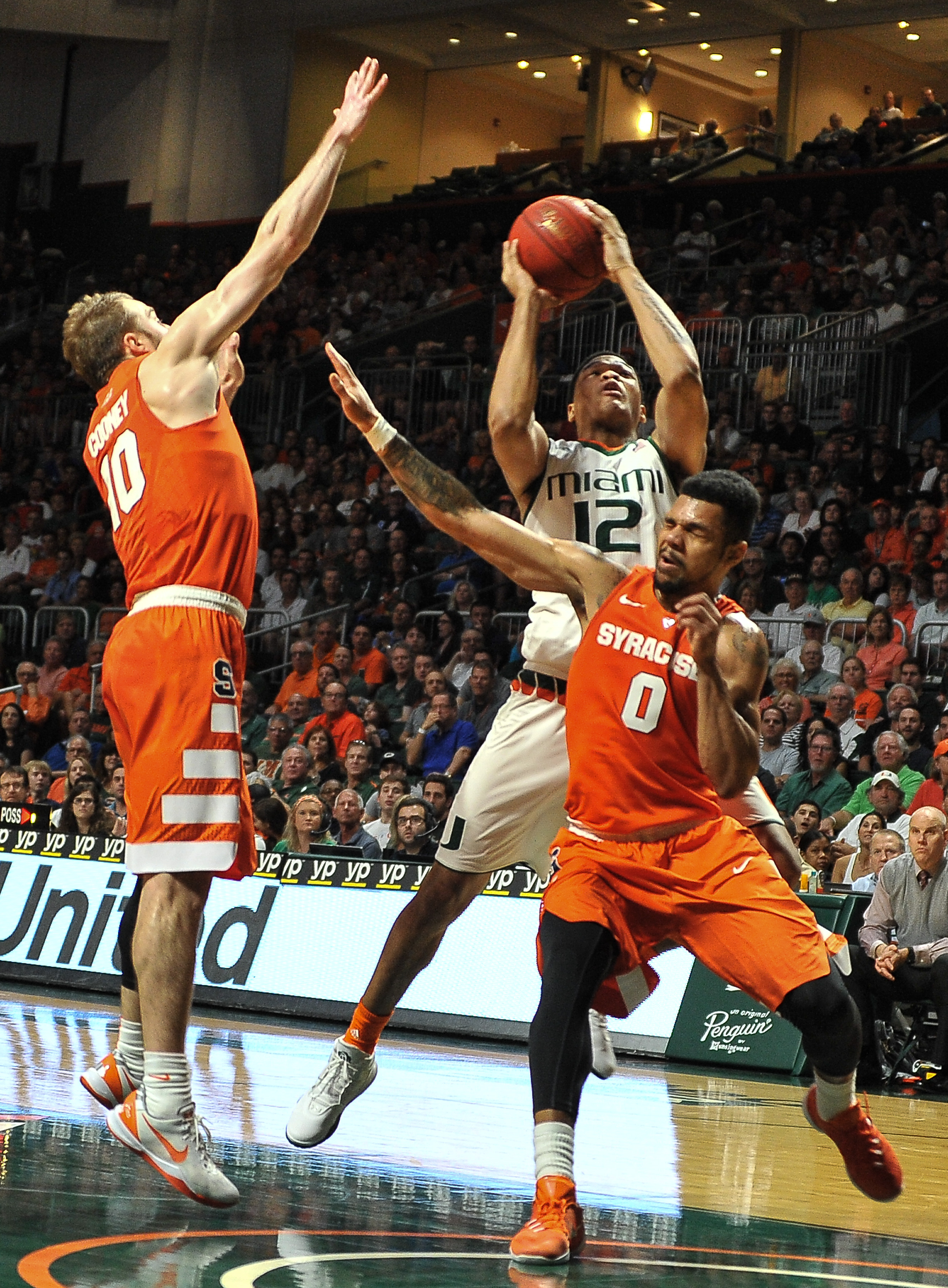 Miami James Palmer goes for shot as Syracuse forward Michael Gbinije and guard Trevor Cooney try to defend during the first half of an NCAA college basketball game in Coral Gables, Fla., Saturday Jan. 2, 2016. (AP Photo/Gaston De Cardenas)