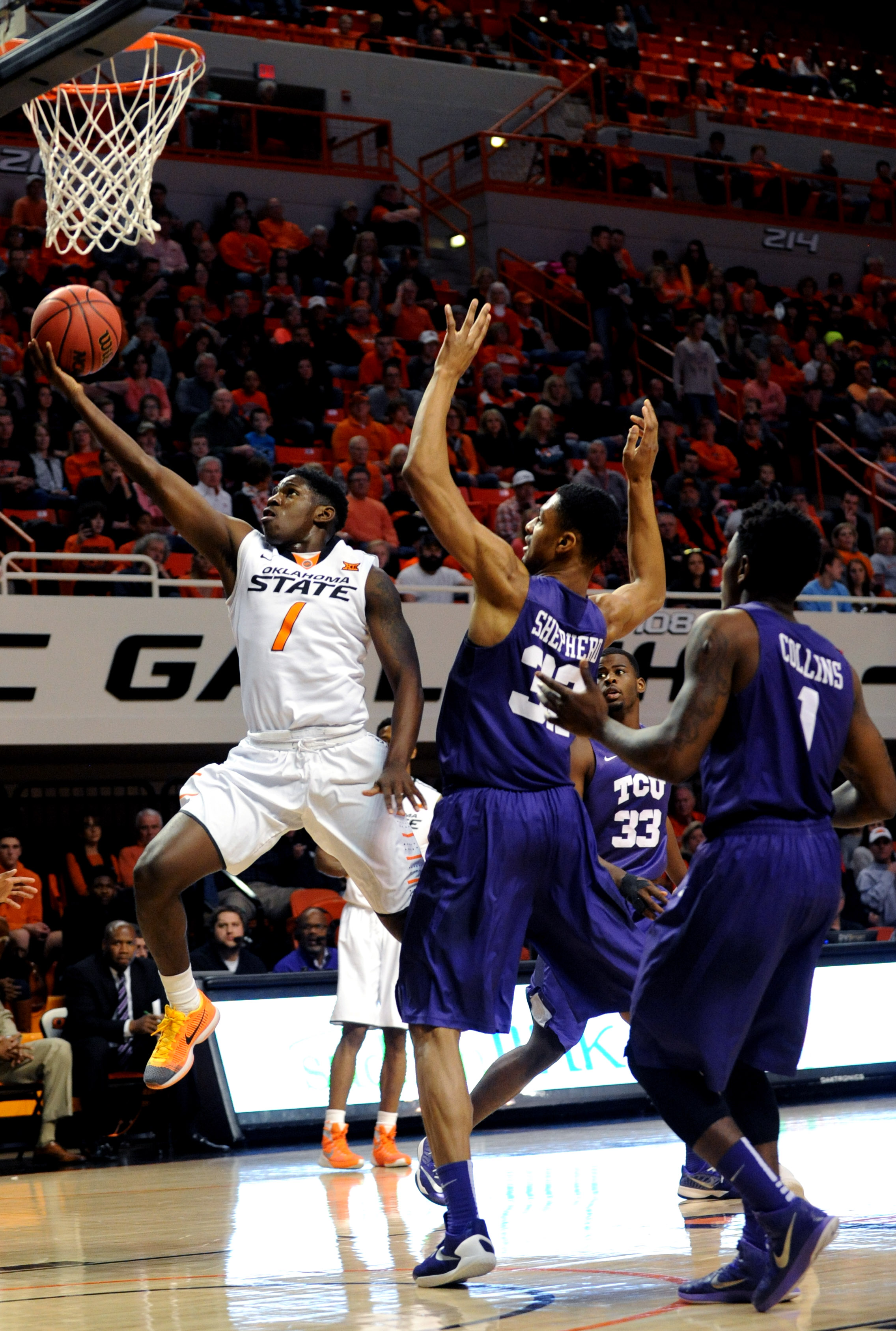 TCU's Karviar Shepherd (32), Chris Washburn (33), and Chauncey Collins (1) watch as Oklahoma State Jawun Evans (1) scores in the first half of an NCAA college basketball game in Stillwater, Okla., Saturday, Jan. 2, 2016. Evans scored a total of 13 points