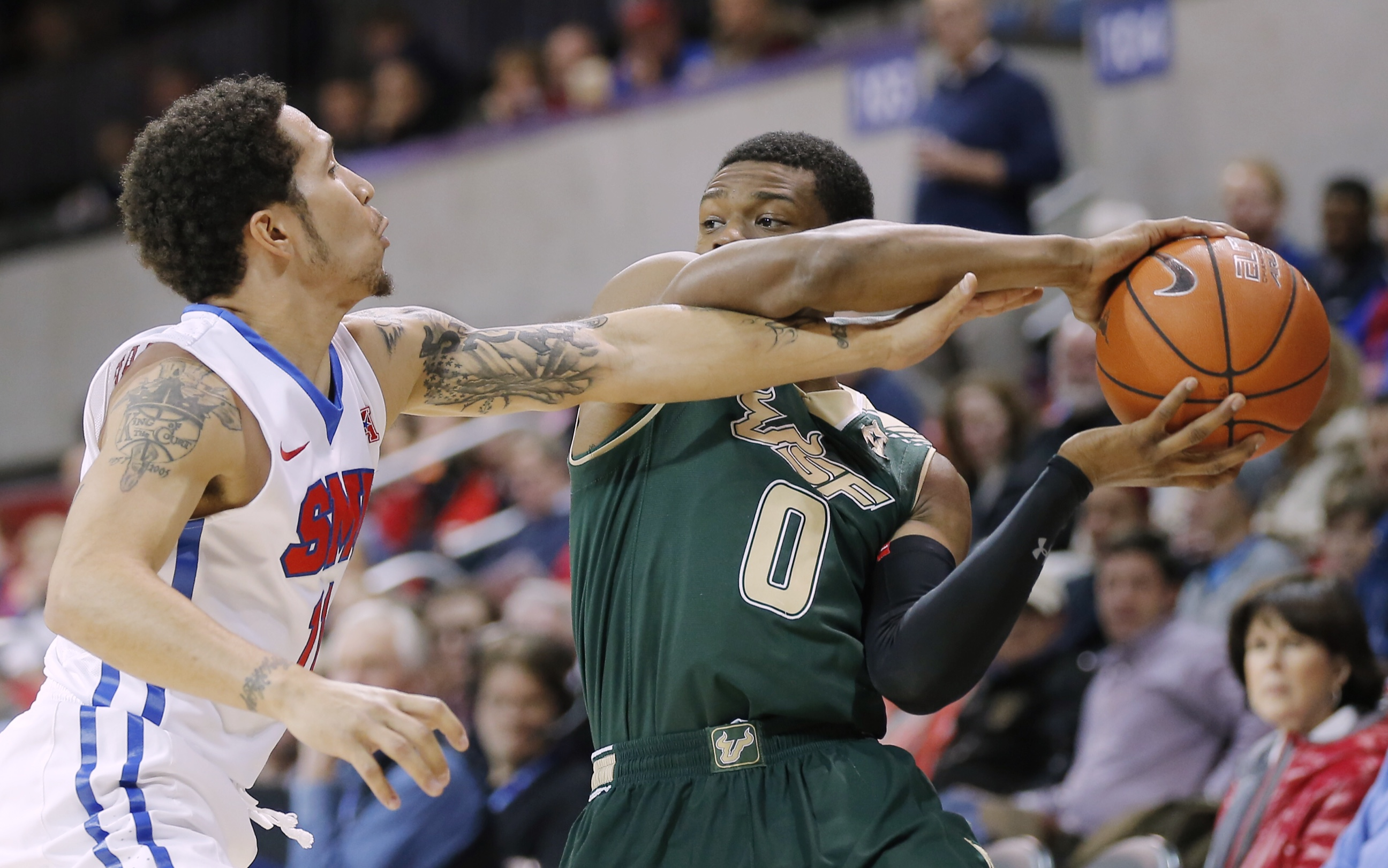 South Florida guard Jahmal McMurray (0) battles SMU guard Nic Moore (11) for space during the first half of an NCAA college basketball game Saturday, Jan. 2, 2016, in Dallas. SMU won 72-58. (AP Photo/Brandon Wade)
