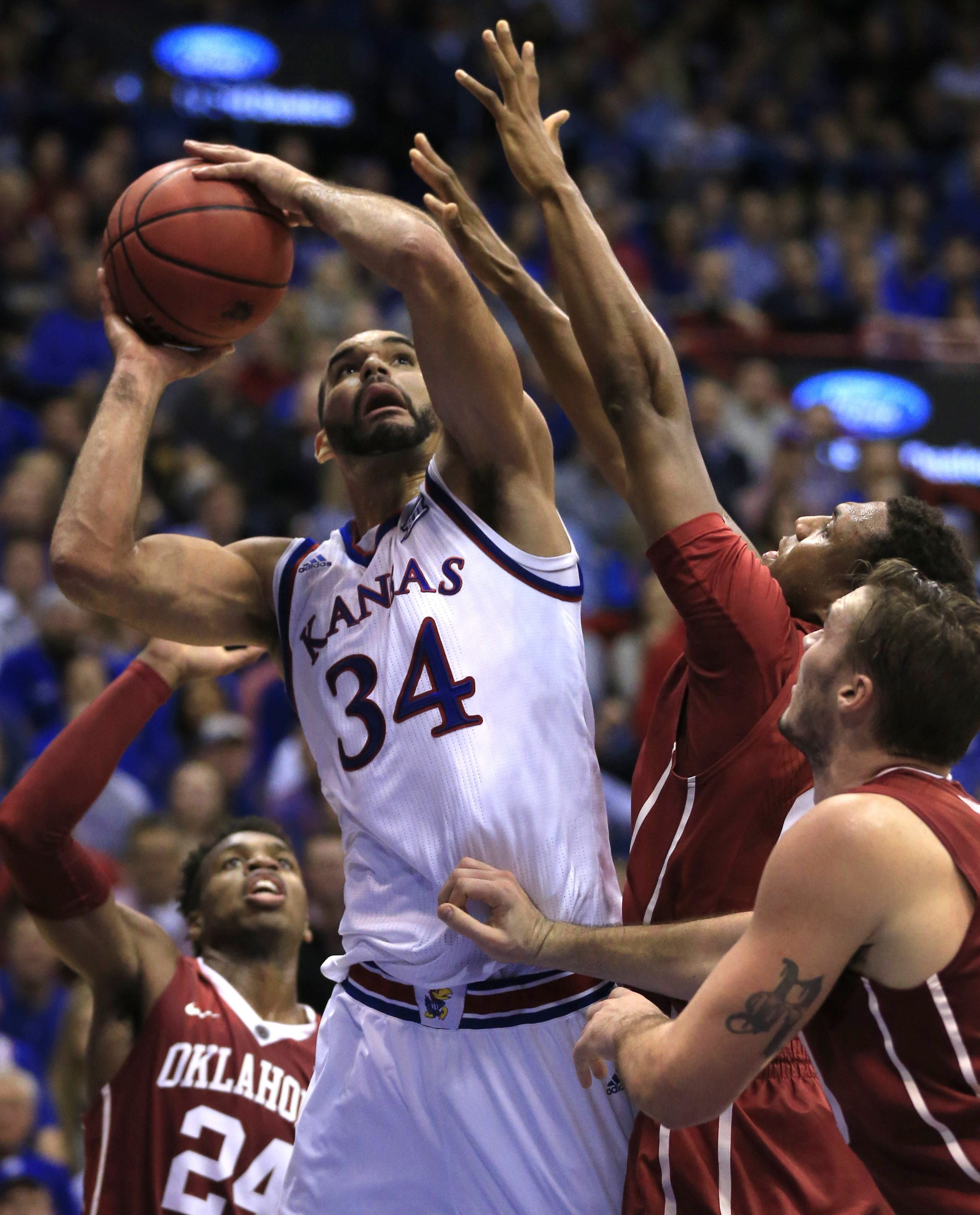 Kansas forward Perry Ellis (34) shoots while covered by three Oklahoma defenders during the first half of an NCAA college basketball game in Lawrence, Kan., Monday, Jan. 4, 2016. (AP Photo/Orlin Wagner)