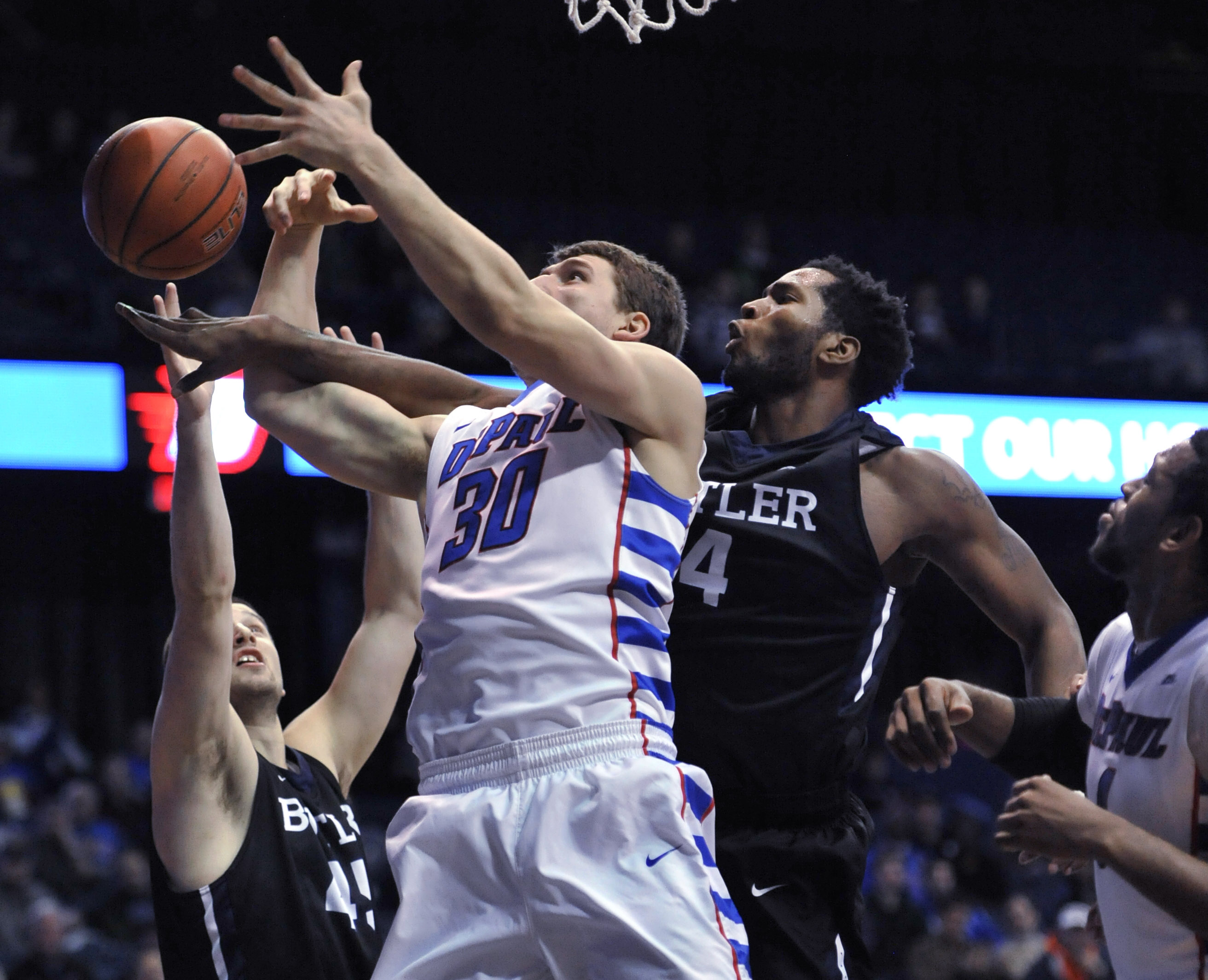 DePaul's Peter Ryckbosch (30), goes up for a rebound against Butler's Tyler Wideman (4), and Andrew Chrabascz (45), while DePaul's Myke Henry (4), looks on during the first half of an NCAA college basketball game, Tuesday, Jan. 5, 2016, in Rosemont, Ill.