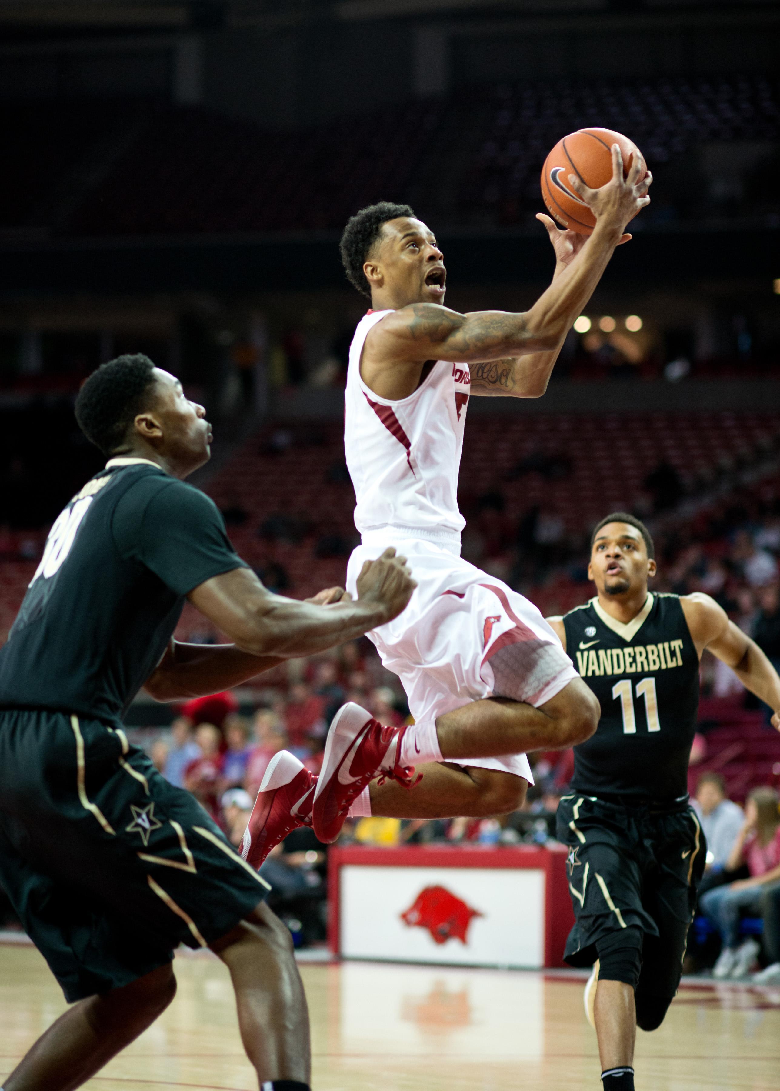 Arkansas' Athlon Bell (5) shoots a basket over Vanderbilt's Damian Jones (30) Jeff Roberson (11), right, in the first half of an NCAA college basketball game in Fayetteville, Ark., Tuesday, Jan. 5, 2016. (AP Photo/Sarah Bentham)