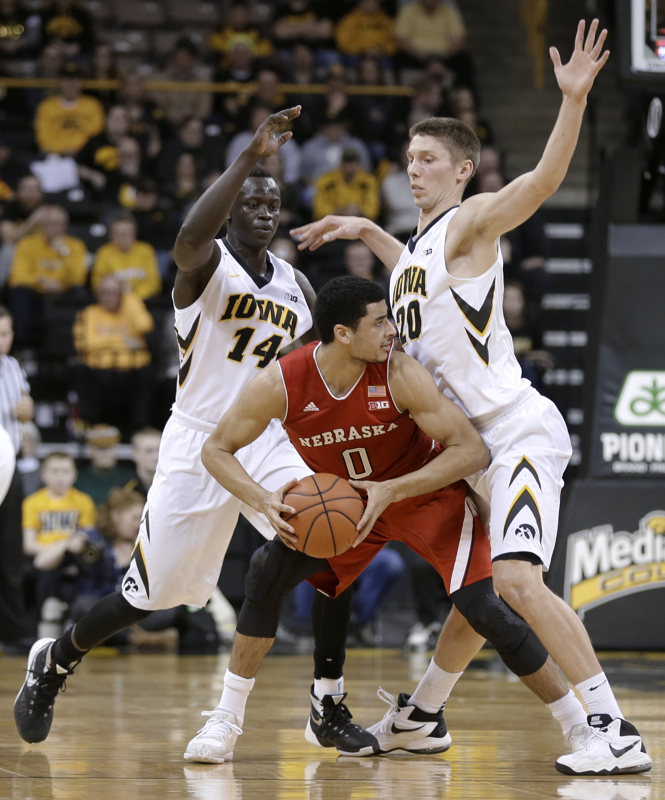 Nebraska's Tai Webster (0) looks to break the pressure defense by Iowa's Peter Jok, left, and Jarrod Uthoff during the first half of an NCAA college basketball game Tuesday, Jan. 5, 2016, in Iowa City, Iowa. (AP Photo/Charlie Neibergall)