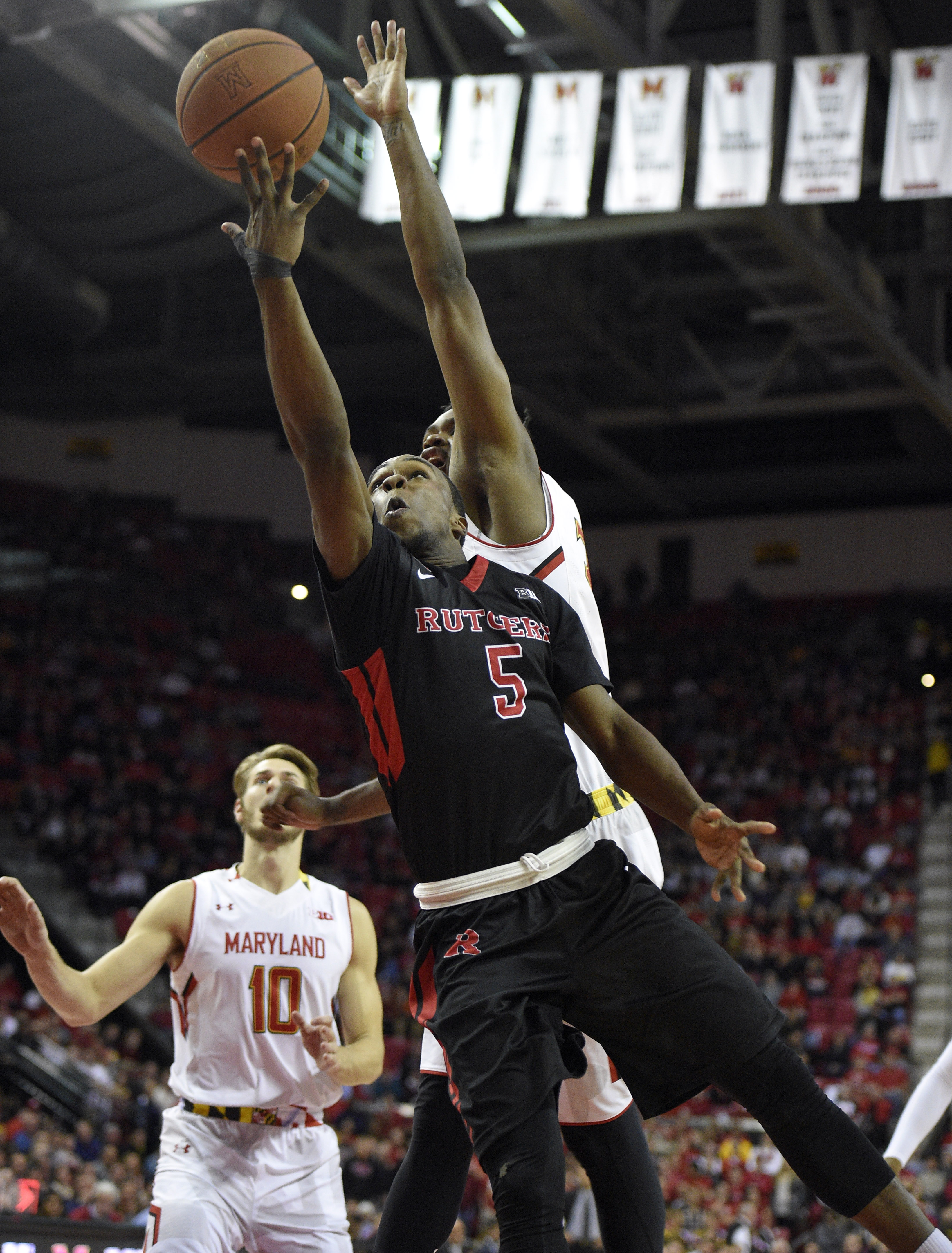 Rutgers guard Mike Williams (5) releases the ball next to the outstretched arm of Maryland center Diamond Stone, back right, as forward Jake Layman (10) watches during the first half of an NCAA college basketball game, Wednesday, Jan. 6, 2016, in College