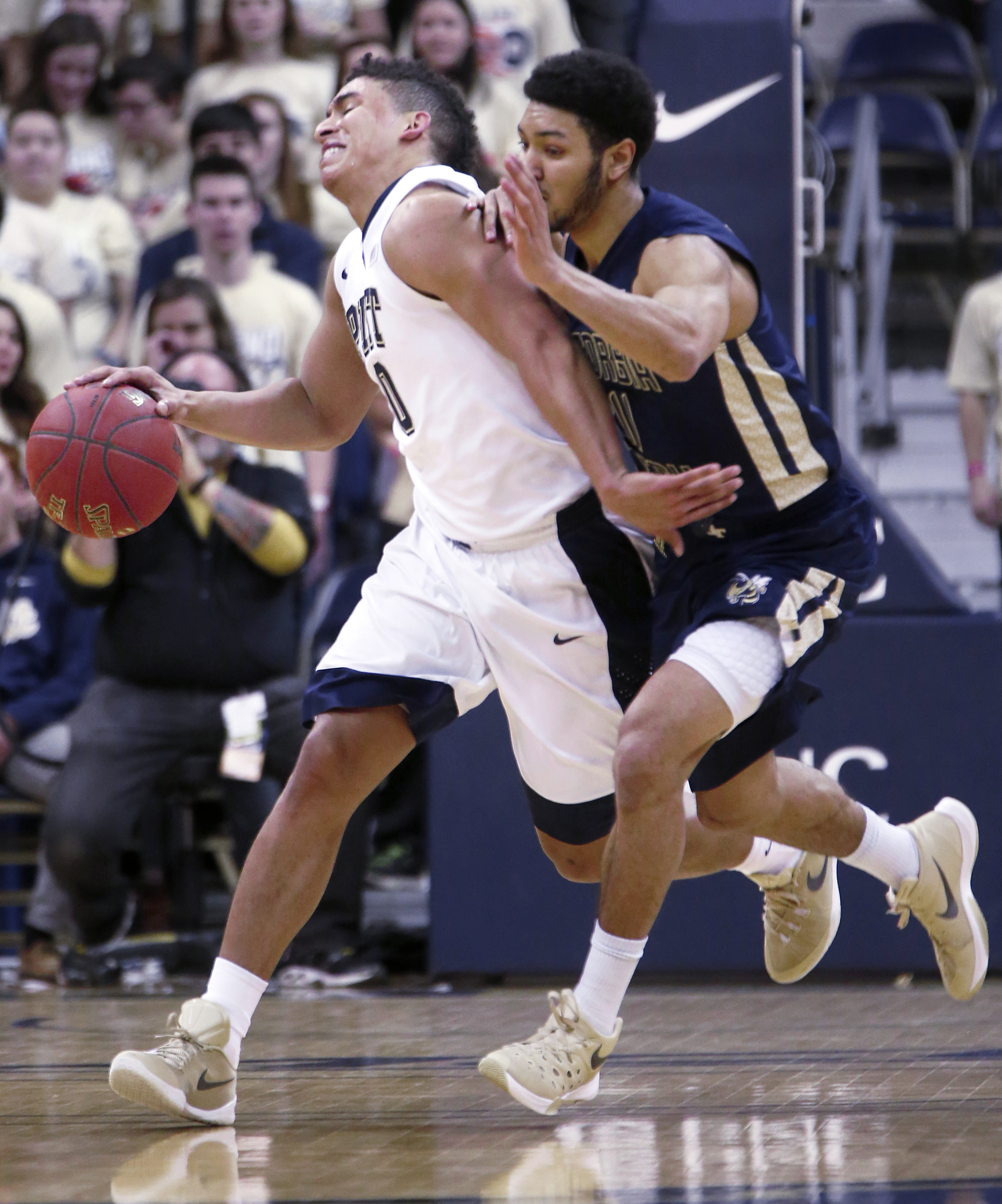Pittsburgh's James Robinson, left,  brings the ball down the court as Georgia Tech's Josh Heath defends during the first half of an NCAA college basketball game, Wednesday, Jan. 6, 2016, in Pittsburgh. (AP Photo/Keith Srakocic)