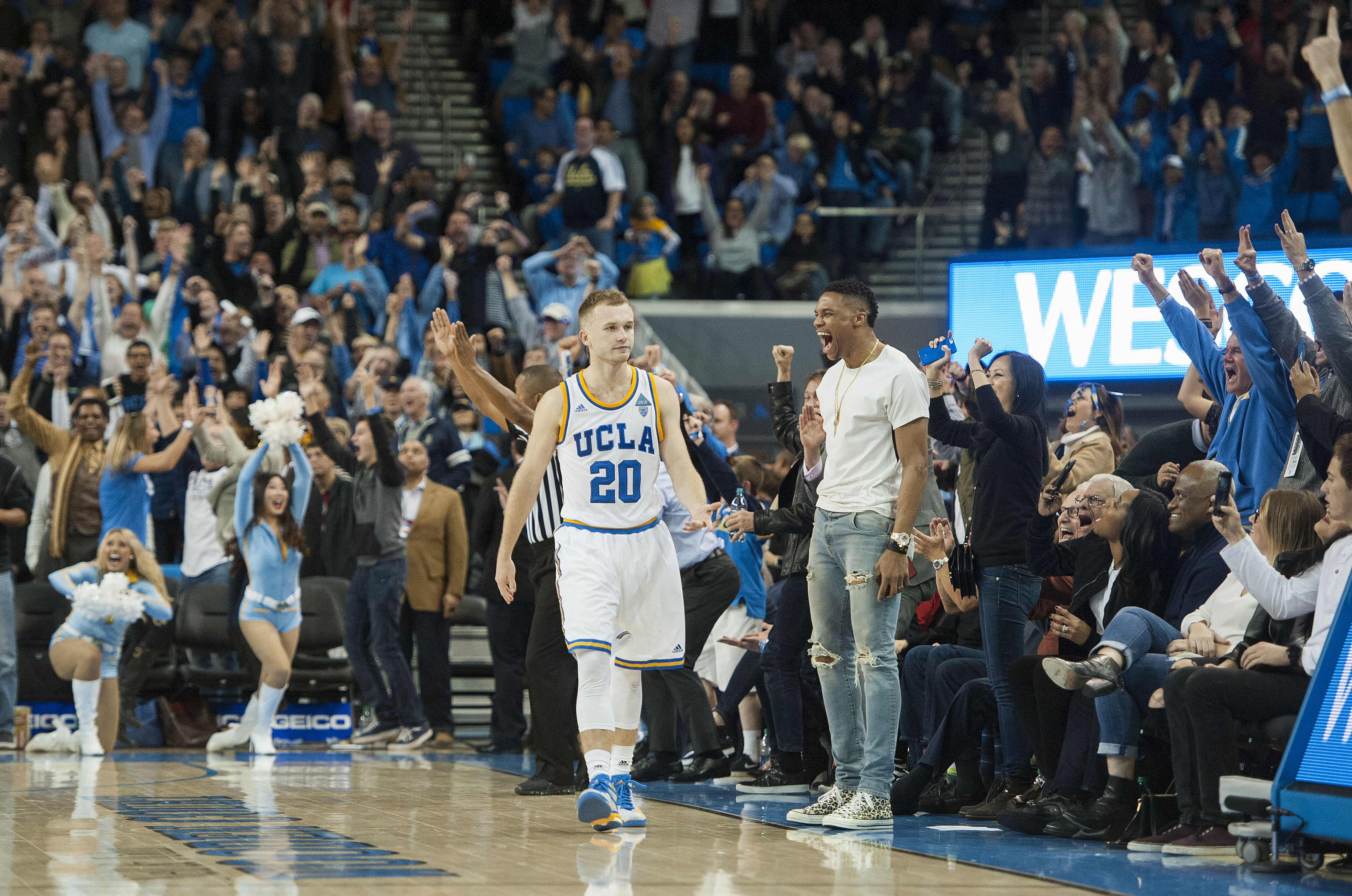 Oklahoma Cirty Thunder's Russell Westbrook joins the crowd in celebrating after UCLA's Bryce Alford (20) sank a 3-pointer to give UCLA an 87-84 victory over Arizona in an NCAA college basketball game Thursday night, Jan. 7, 2016, in Los Angeles. (Kevin Su
