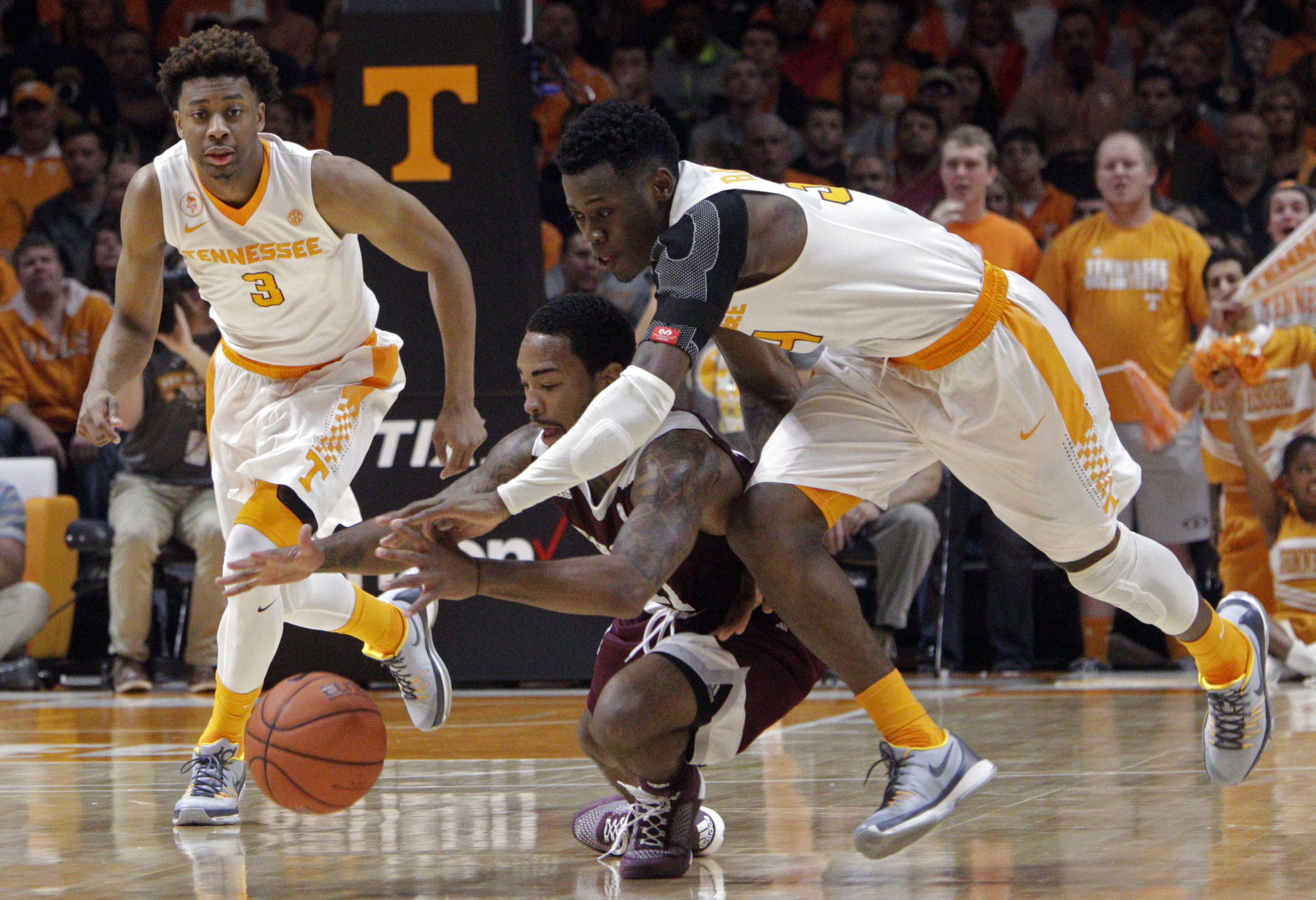 Tennessee guard Devon Baulkman, right, battles for the ball with Texas A&M guard Anthony Collins (11) during the first half of an NCAA college basketball game Saturday, Jan. 9, 2016, in Knoxville, Tenn. Tennessee guard Robert Hubbs III (3) trails. (AP Pho