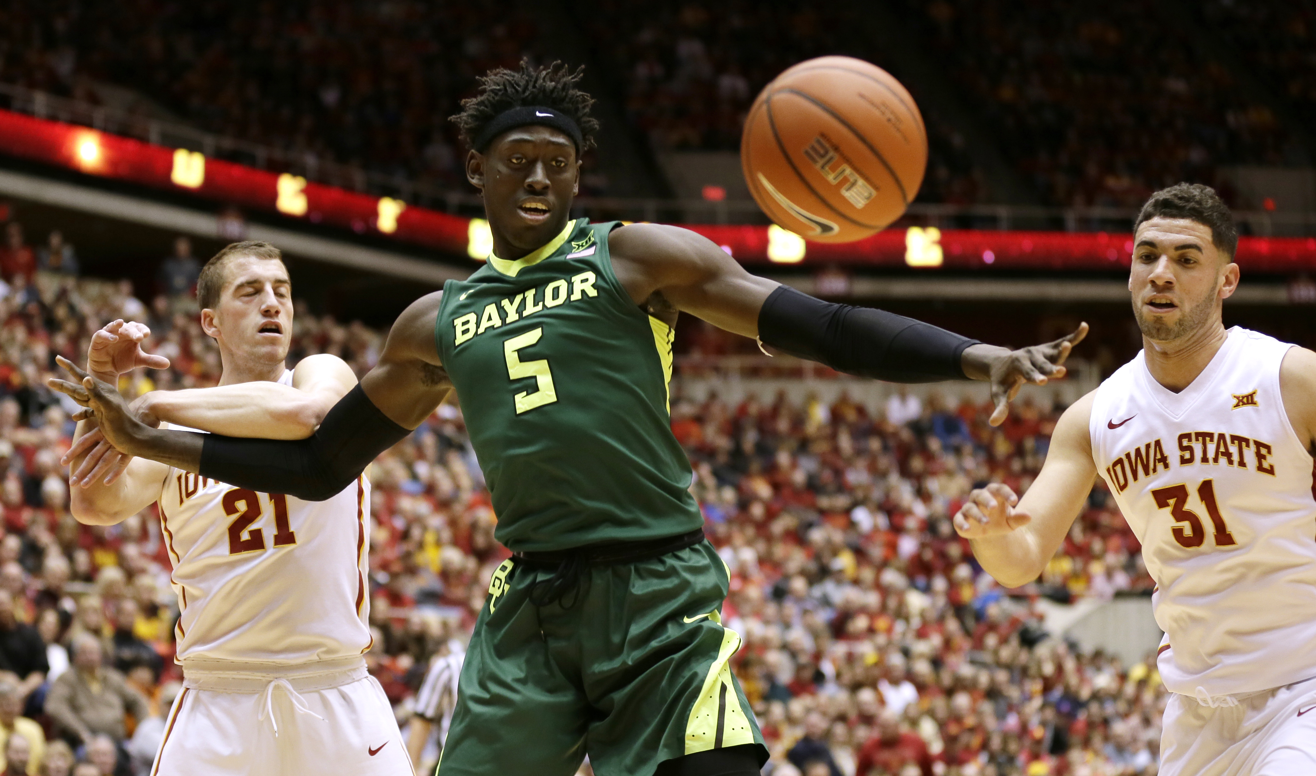Baylor forward Johnathan Motley (5) fights for a loose ball with Iowa State's Matt Thomas, left, and Georges Niang, right, during the first half of an NCAA college basketball game, Saturday, Jan. 9, 2016, in Ames, Iowa. (AP Photo/Charlie Neibergall)