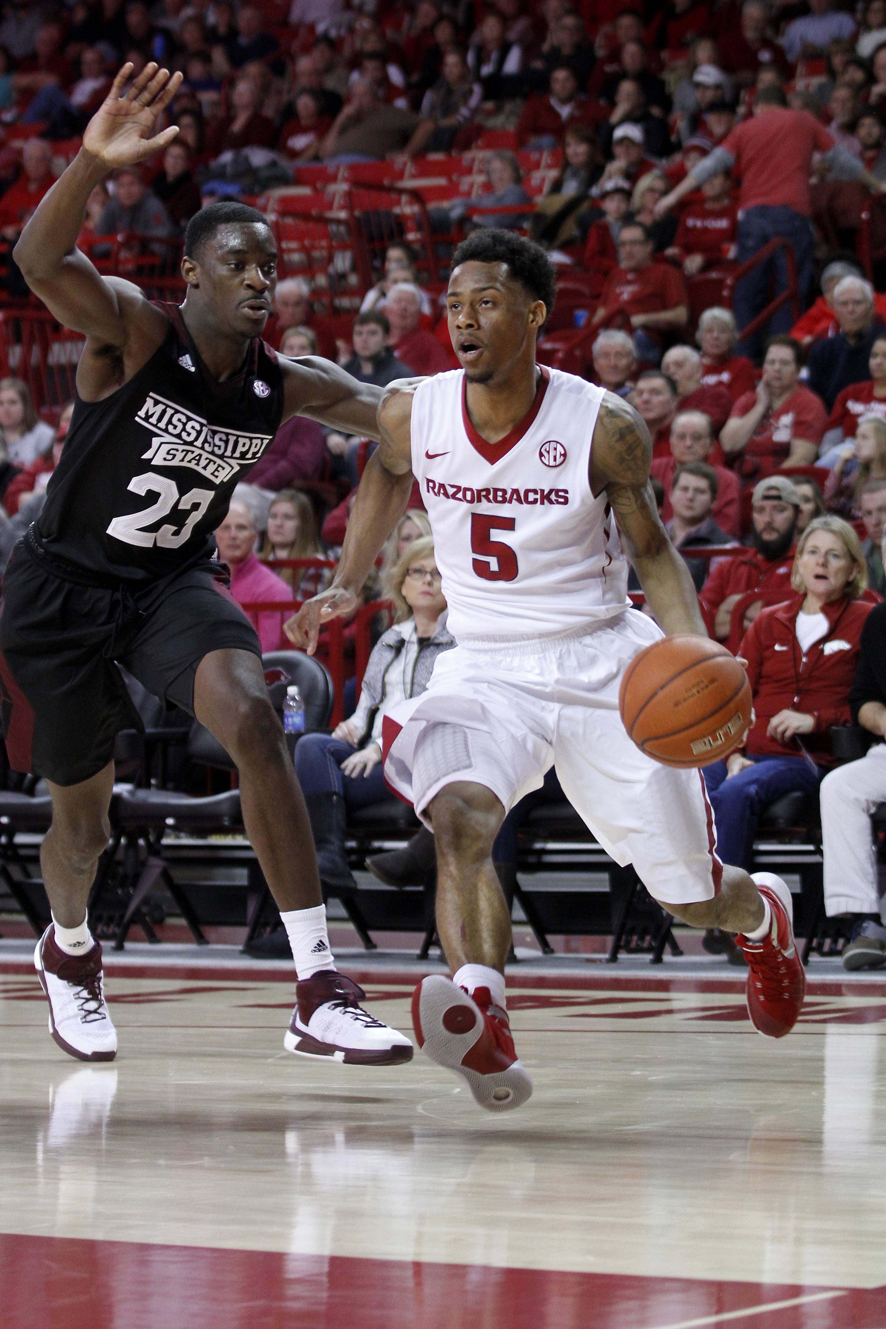Arkansas' Anthlon Bell (5) looks to drive around Mississippi State's Travis Daniels (23) during the first half of an NCAA college basketball game Saturday, Jan. 9, 2016, in Fayetteville, Ark. (AP Photo/Samantha Baker)