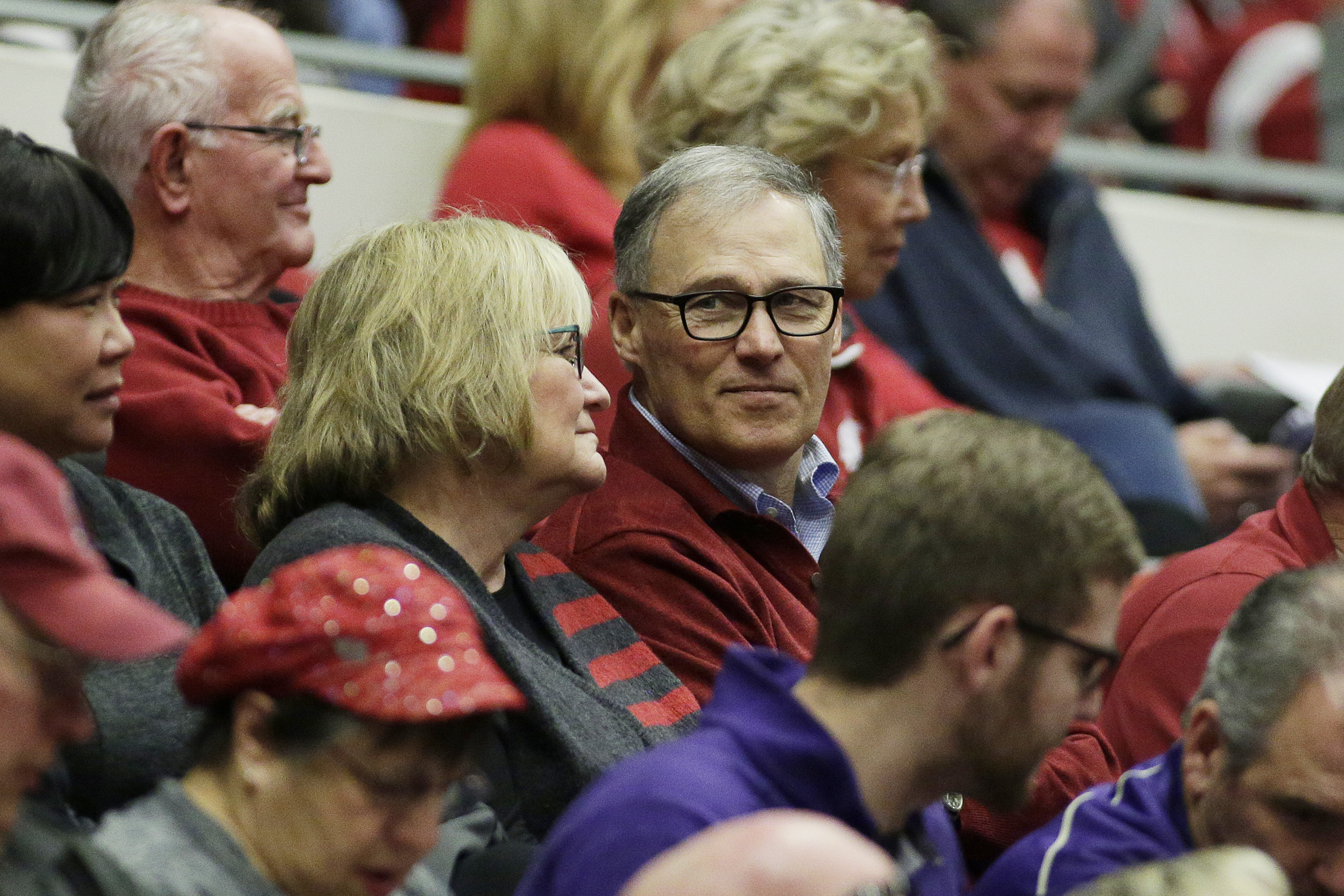 Washington Governor Jay Inslee, right, speaks with his wife Trudi during the first half of an NCAA college basketball game between Washington State and Washington, Saturday, Jan. 9, 2016, in Pullman, Wash. (AP Photo/Young Kwak)