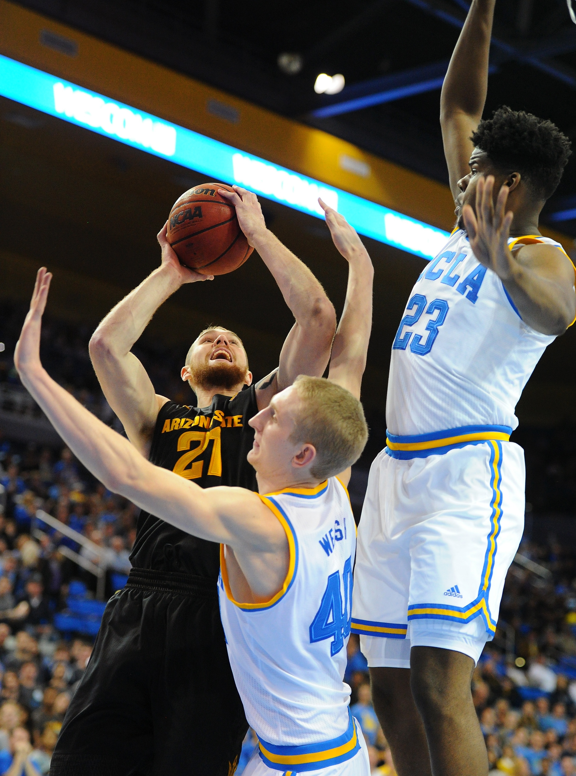 Arizona State's Eric Jacobsen (21) goes to the basket against UCLA's Thomas Welsh, bottom left, and Tony Parker (23) in the first half of an NCAA college basketball game in Los Angeles, Saturday, Jan. 9, 2016. (AP Photo/Michael Owen Baker)
