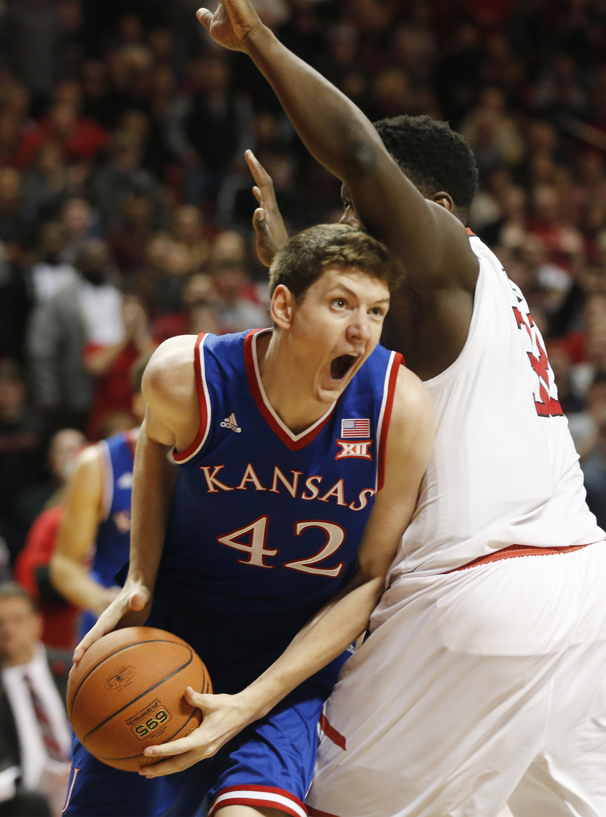 Kansas forward Hunter Mickelson, left, drives under Texas Tech center Norense Odiase in the first period  during an NCAA college basketball game Saturday, Jan. 9, 2016,  in Lubbock, Texas.  (AP Photo/Mark Rogers)