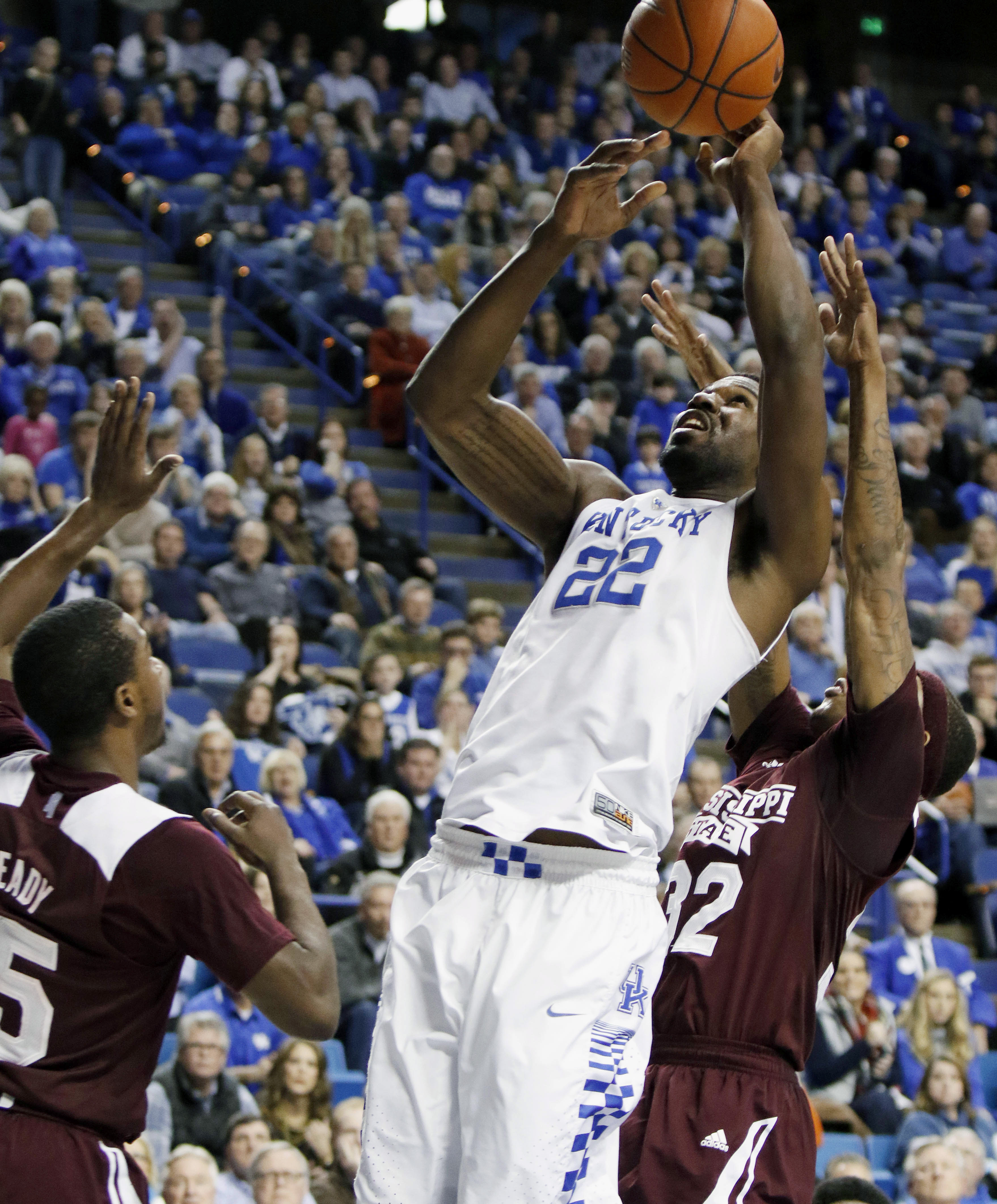 Kentucky's Alex Poythress (22) shoots between Mississippi State's I.J. Ready, left, and Craig Sword during the second half of an NCAA college basketball game Tuesday, Jan. 12, 2016, in Lexington, Ky. Kentucky won 80-74. (AP Photo/James Crisp)