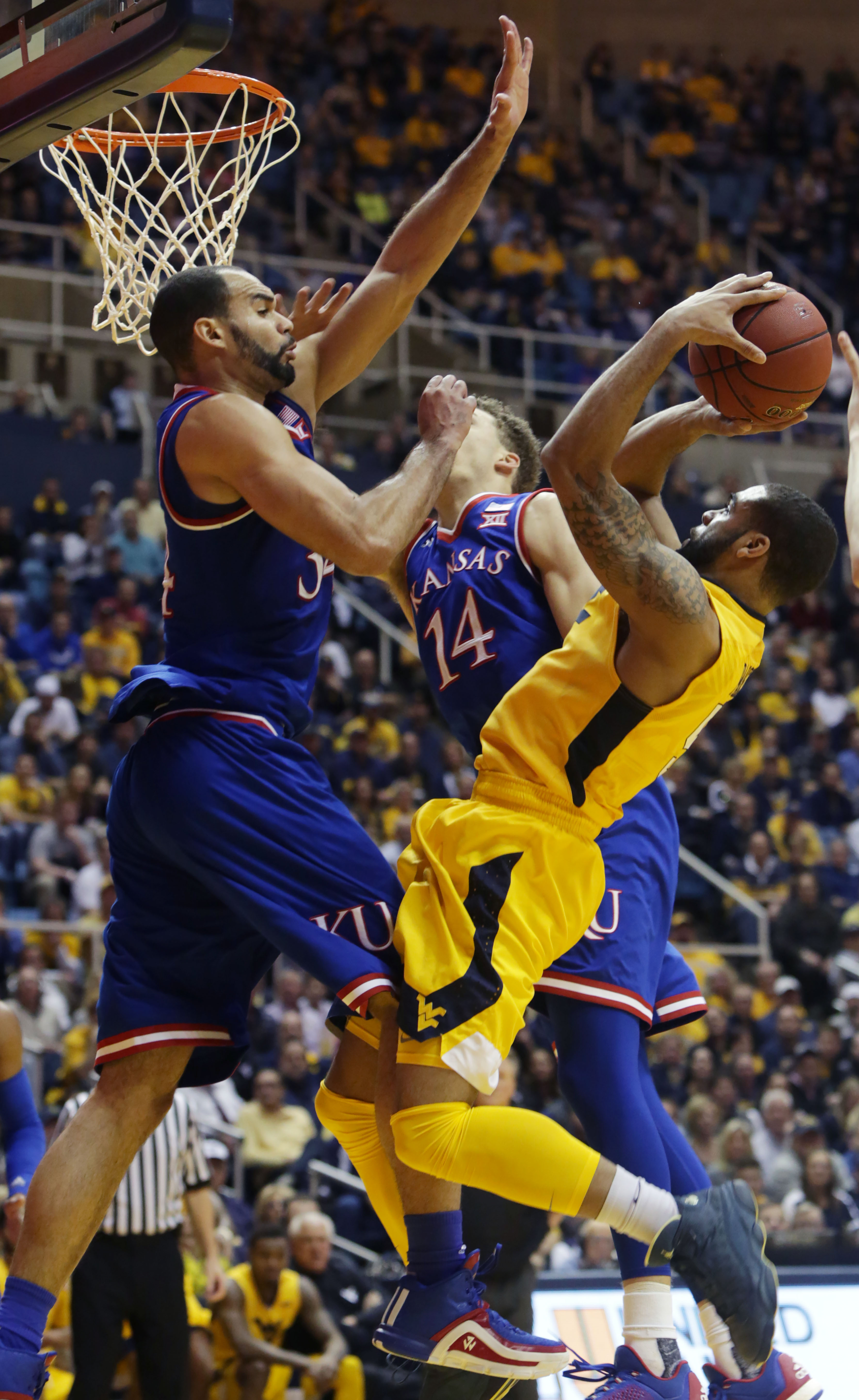 West Virginia guard Jaysean Paige (5) takes a shot while being defended by Kansas forward Perry Ellis (34) during the second half of an NCAA college basketball game, Tuesday, Jan, 12, 2016, in Morgantown, W.Va. West Virginia defeated Kansas 74-63. (AP Pho